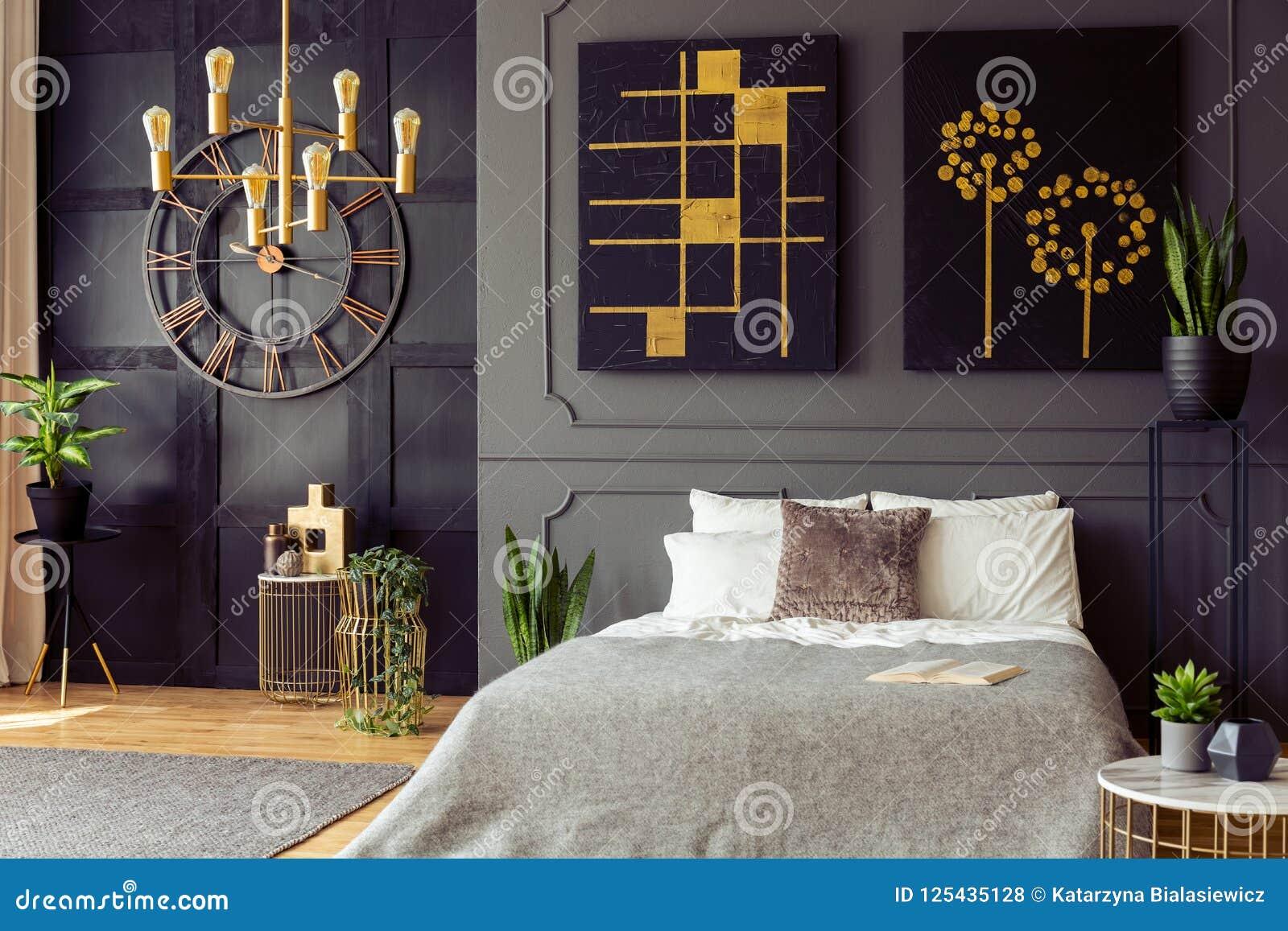 Заводы и чернота и плакаты золота в сером интерьере спальни с часами и кровати с подушками Реальное фото