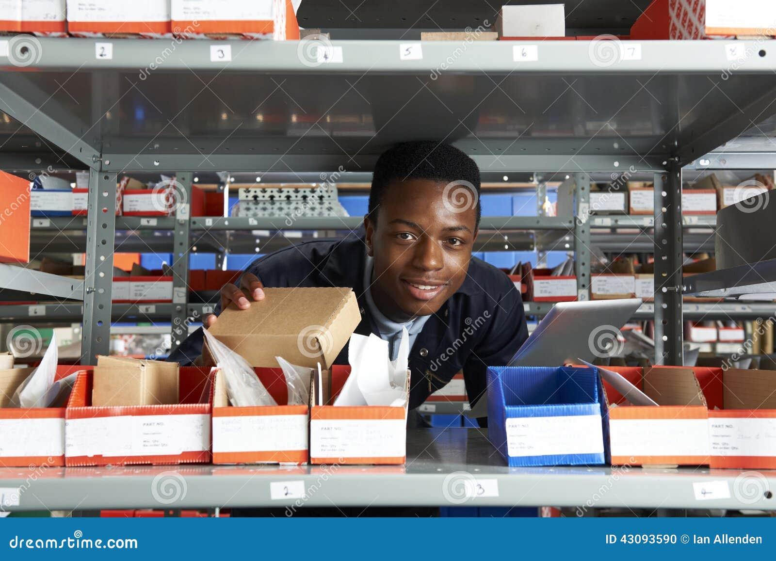 Заводской рабочий используя таблетку цифров в складе
