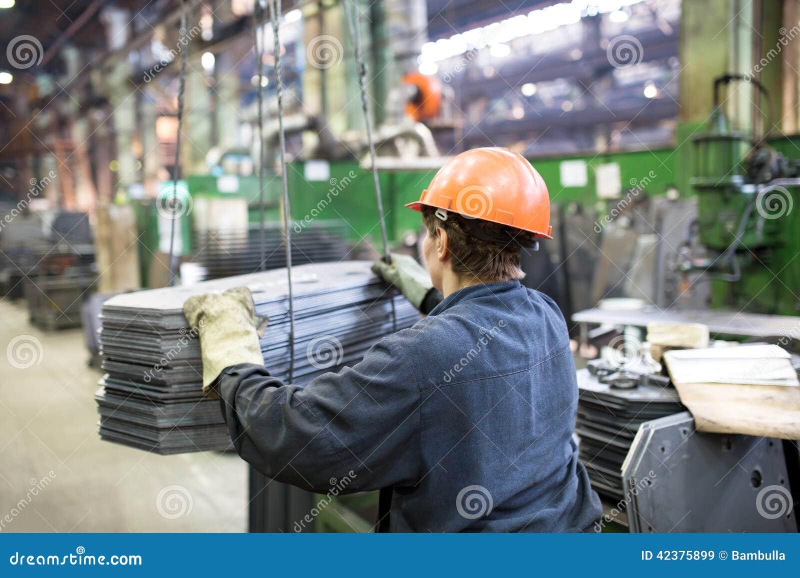 Заводской рабочий транспортируя груз с краном