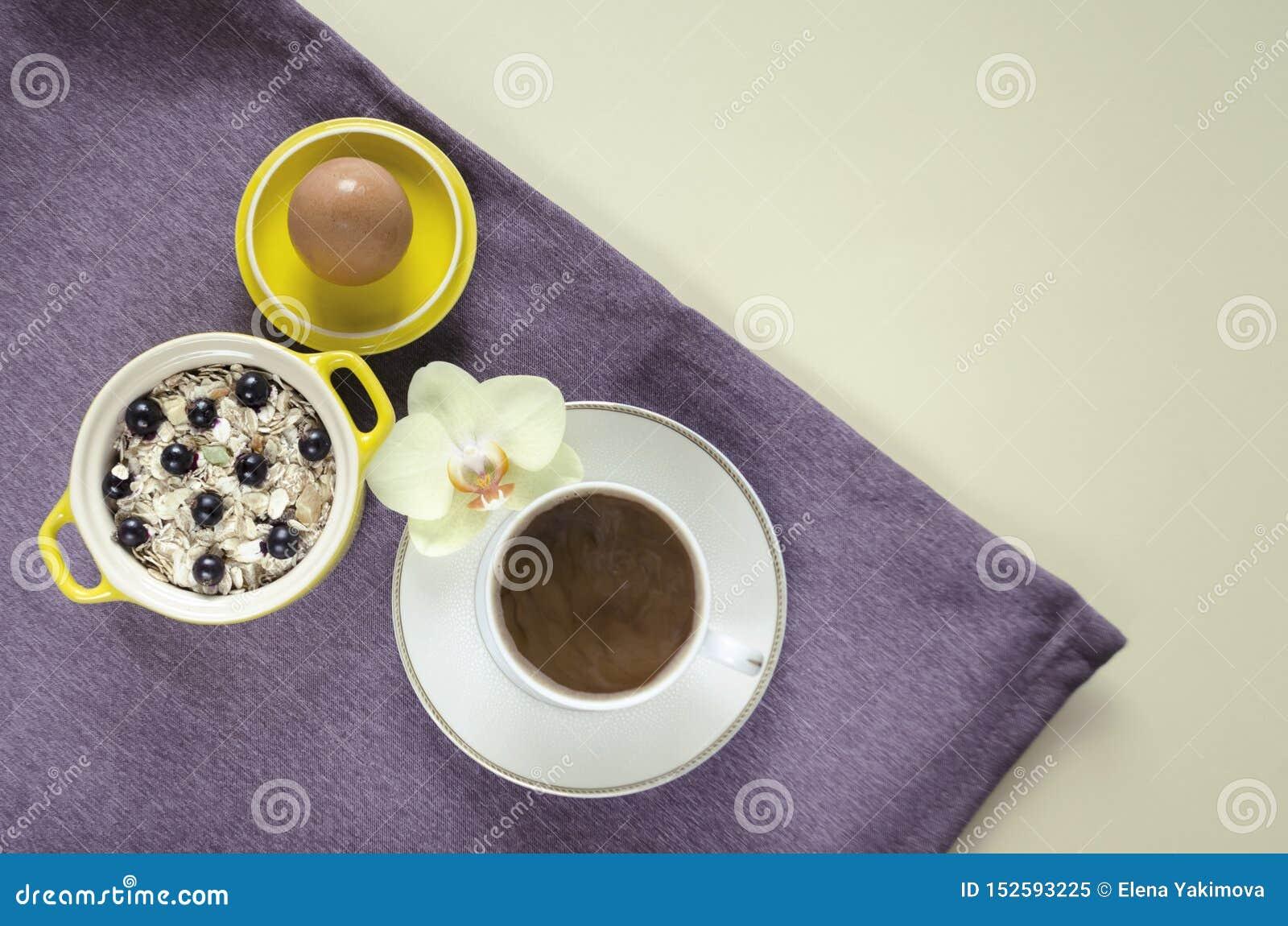 Завтрак в кровати взгляд сверху на подносе овсяной каши в желтом баке, muesli со свежими голубиками, яйца, кофе с молоком на пурп