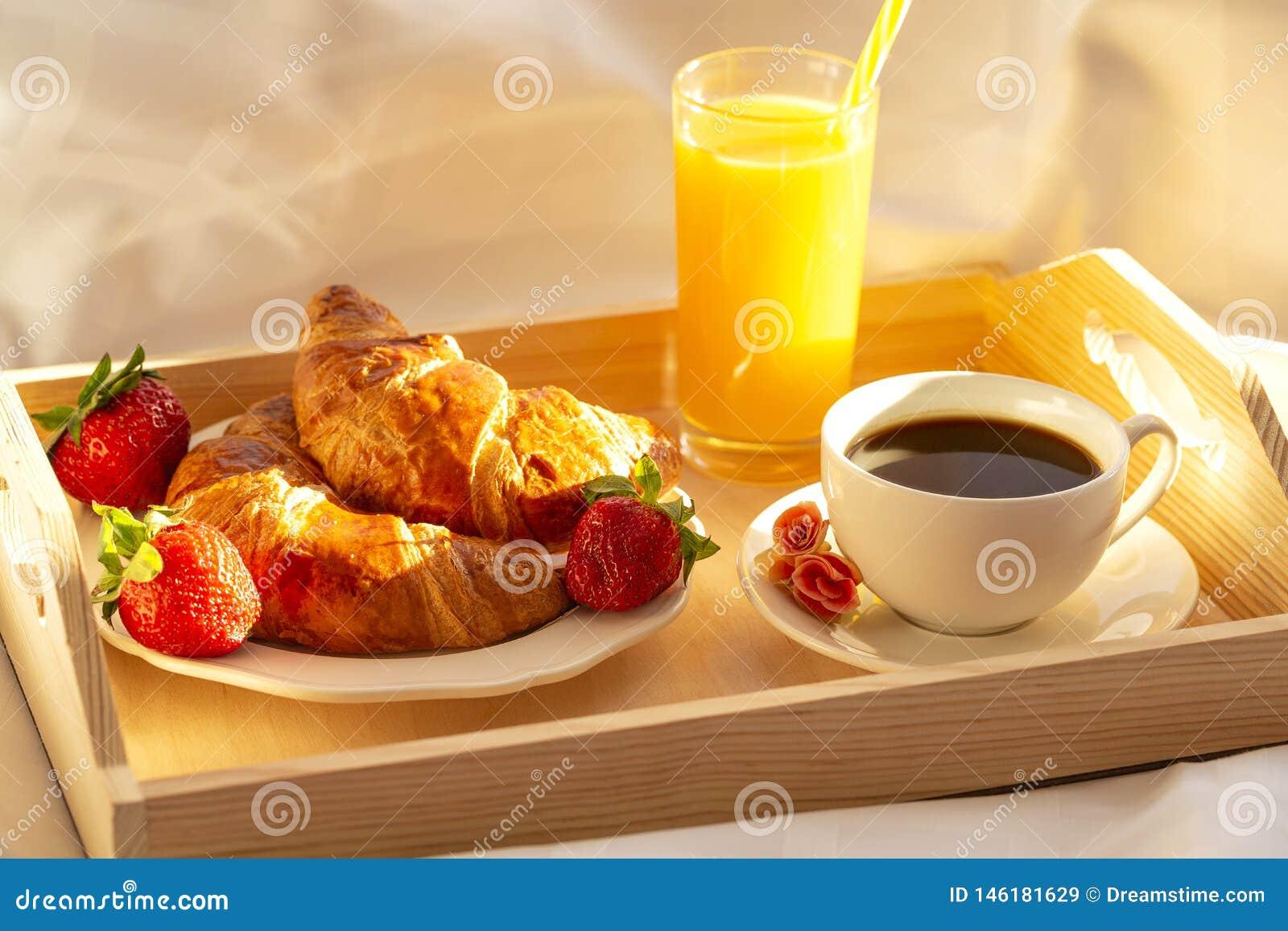 Завтрак в кровати, поднос кофе, круассаны, сок и свежие клубники Раннее утро