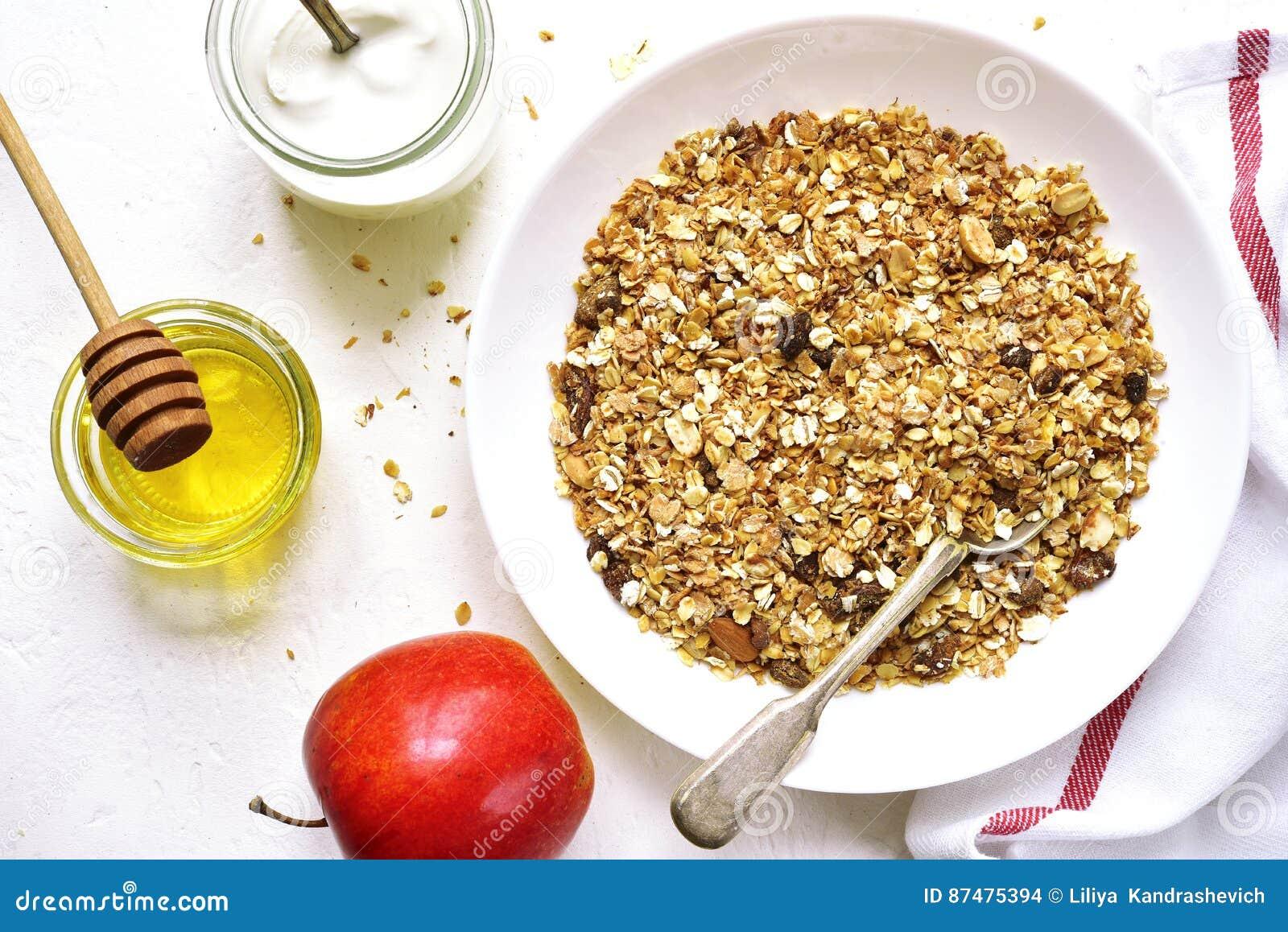 Завтрак здорового питания: granola, плодоовощи, югурт и мед верхняя часть соперничает