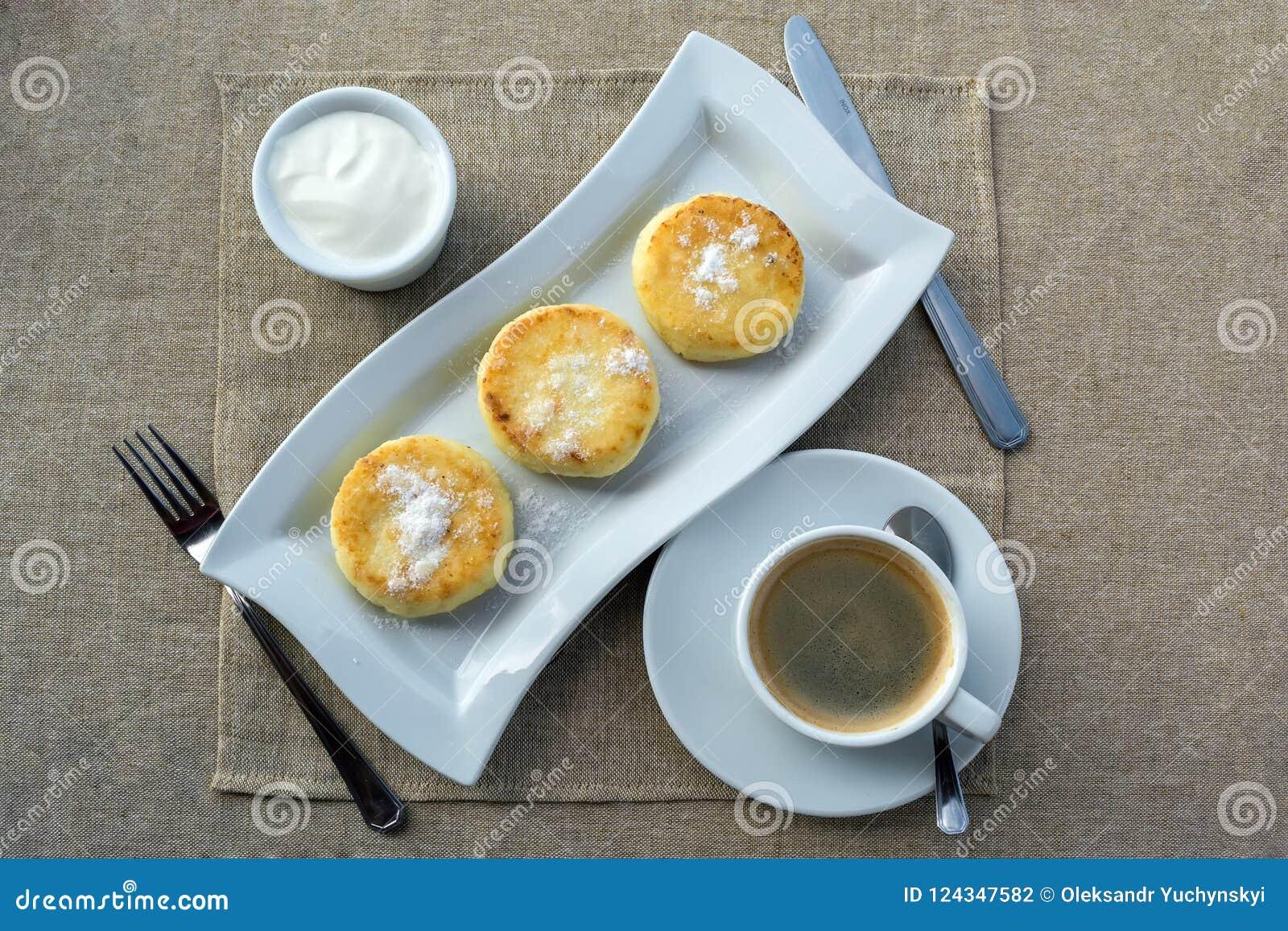 Завтрак состоя из блинчика с сметаной и кофе