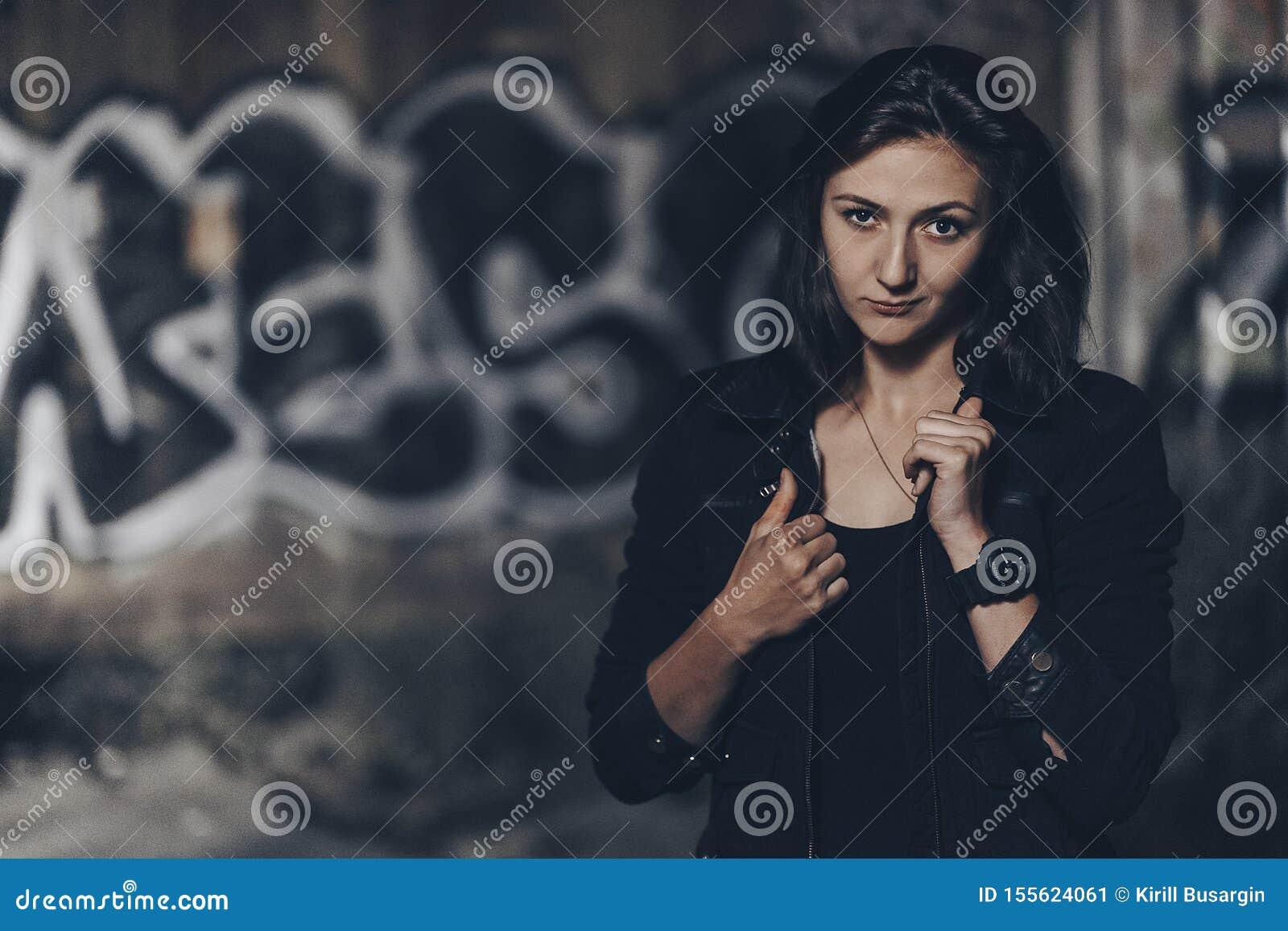 Загадочная красивая женщина в черном bodysuit и кожаная куртка с татуировкой хны на ее ногах сидя на старых каменных шагах с