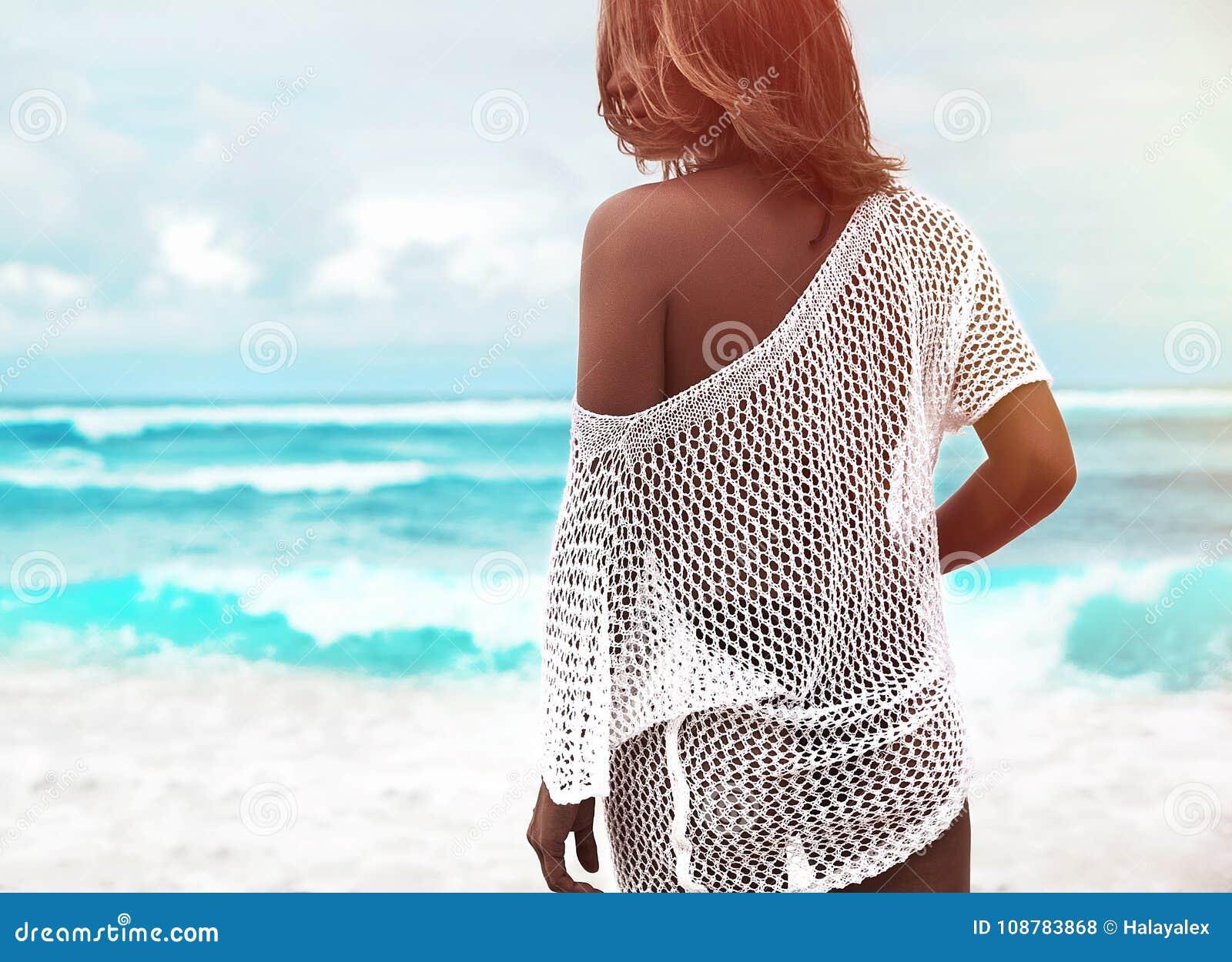 Загоранная модель женщины в прозрачной белой блузке сидя на пляже лета и голубой предпосылке океана