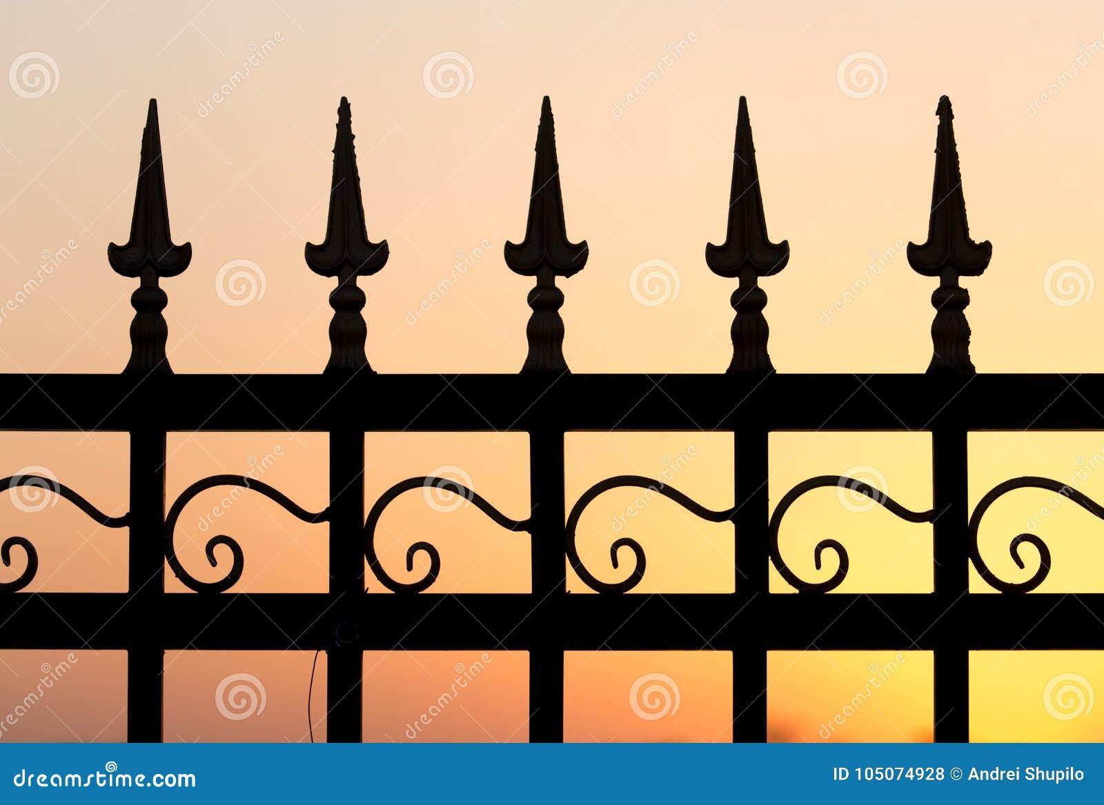 Загородка металла на заходе солнца