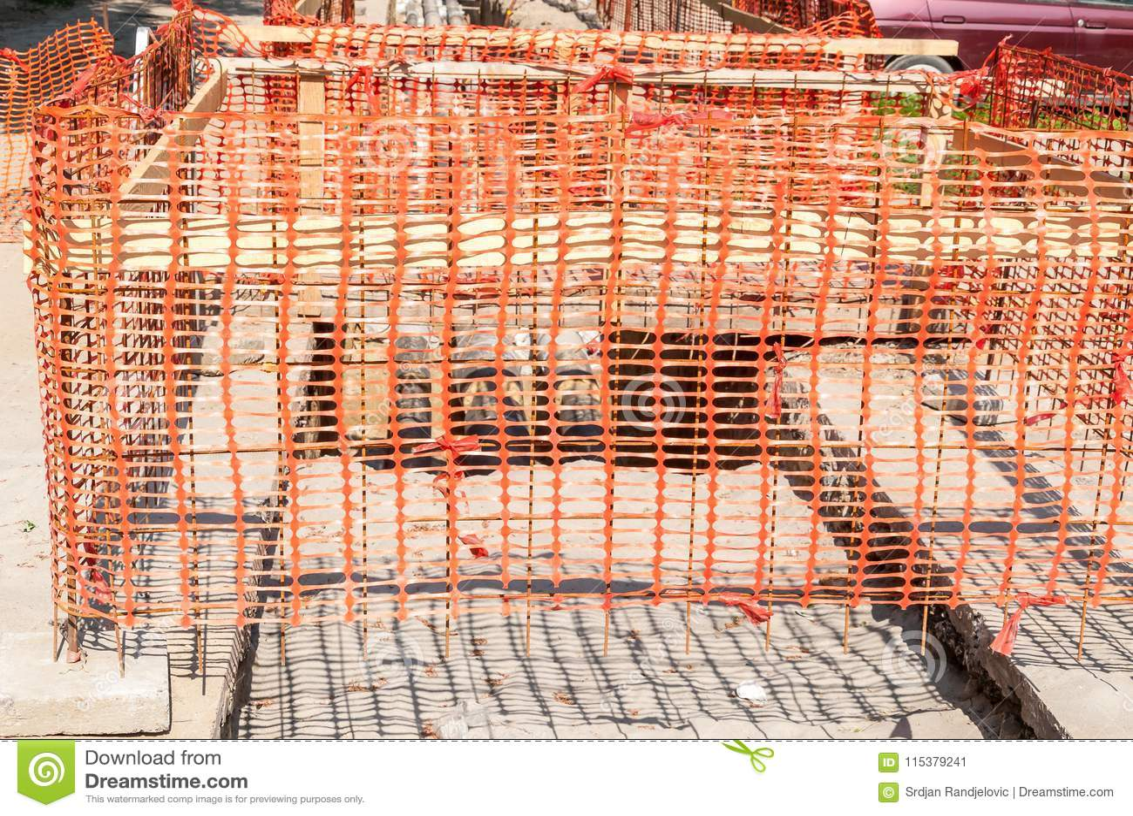 Загородка сети безопасности строительной площадки оранжевая как барьер над канавой на раскопк улицы