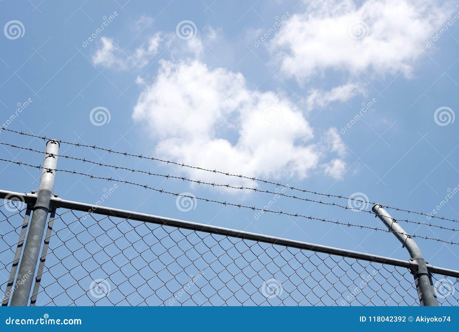 Загородка с колючими проволоками на голубом небе