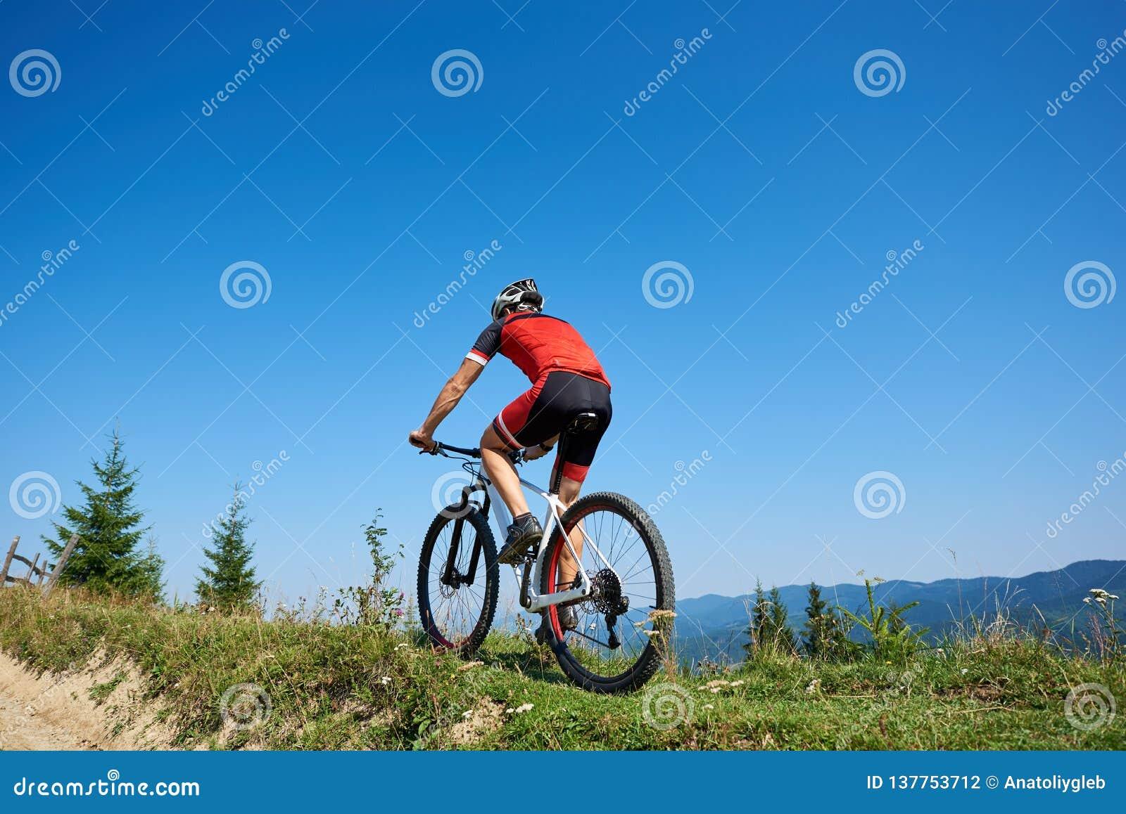Задний взгляд атлетического туристского велосипедиста в велосипеде шлема и полного оборудования задействуя вверх по травянистому