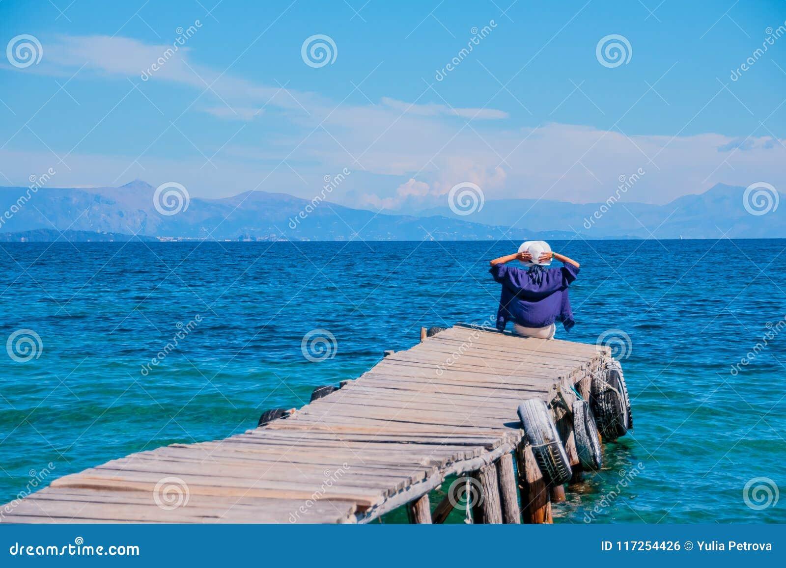 Задний взгляд женщины сидя на крошечной деревянной пристани морем Молодая красивая девушка сидя на моле задний взгляд изумлять
