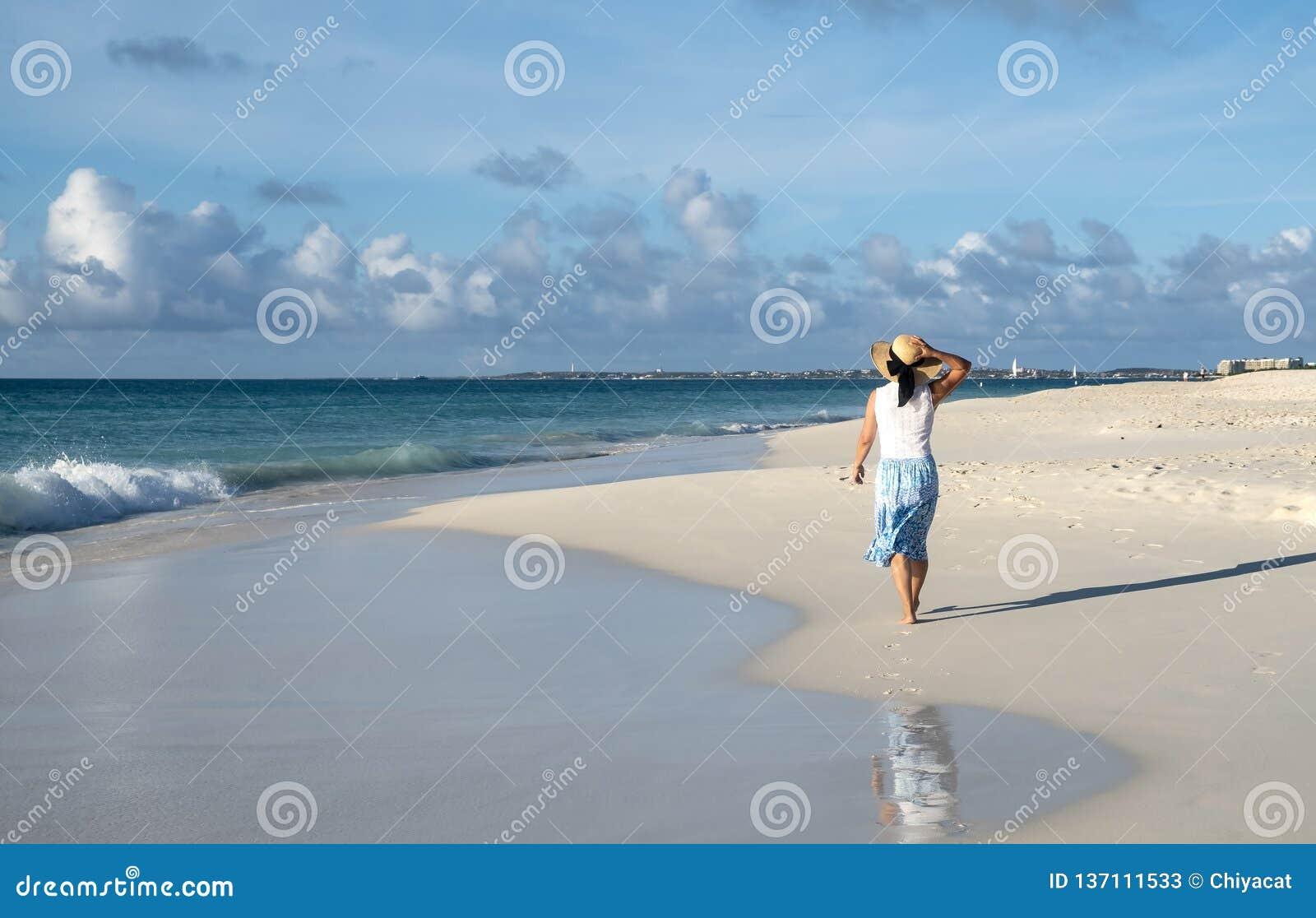 Задний взгляд идти женщины босоногий на карибском пляже 6