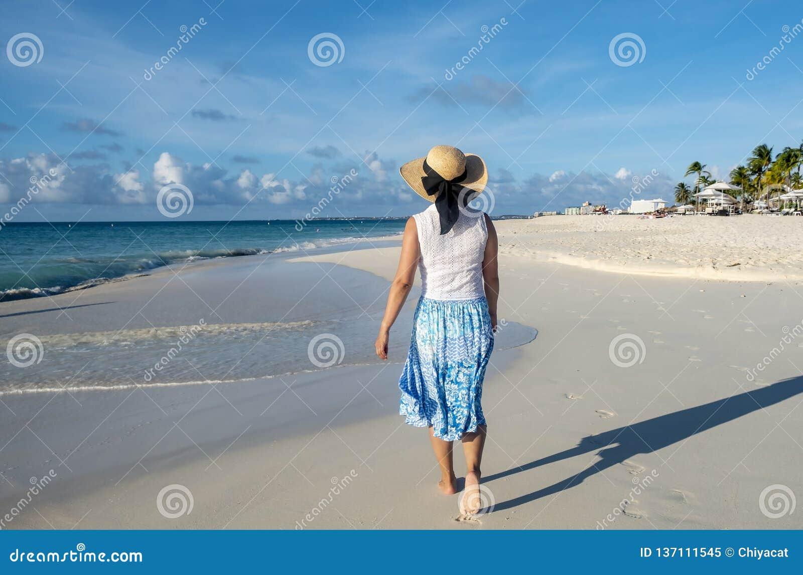 Задний взгляд идти женщины босоногий на карибском пляже 3