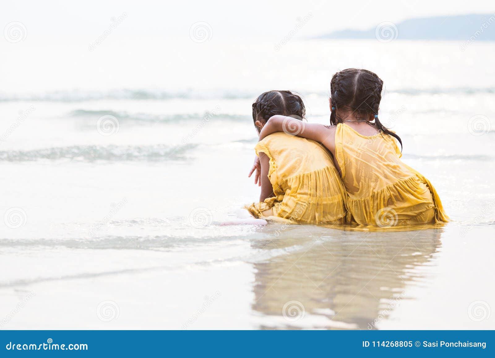 Задний взгляд 2 милых азиатских девушек маленького ребенка обнимая на пляже