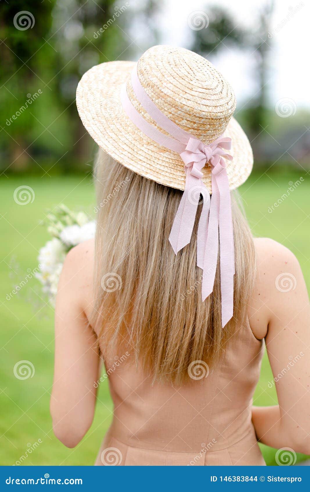 Задний взгляд молодого женского человека в прозодеждах и шляпе пигмента