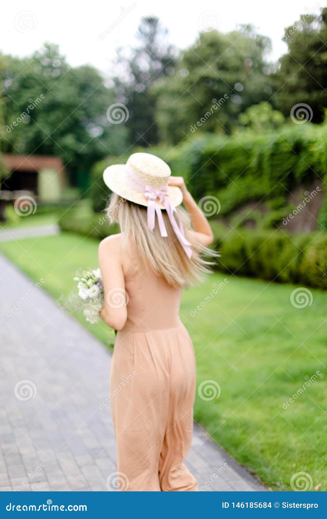 Задний взгляд молодой белокурой женщины в прозодеждах и шляпе пигмента