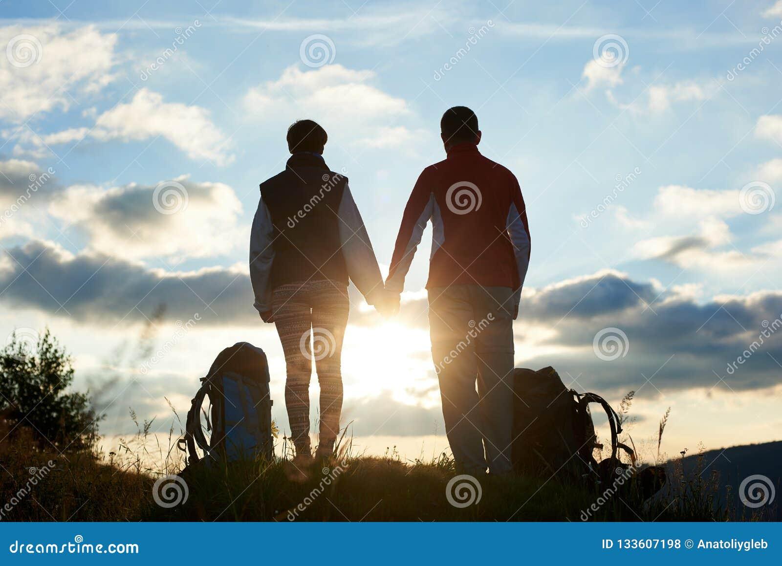 Задний взгляд молодых людей восхищая заход солнца в горах держа руки
