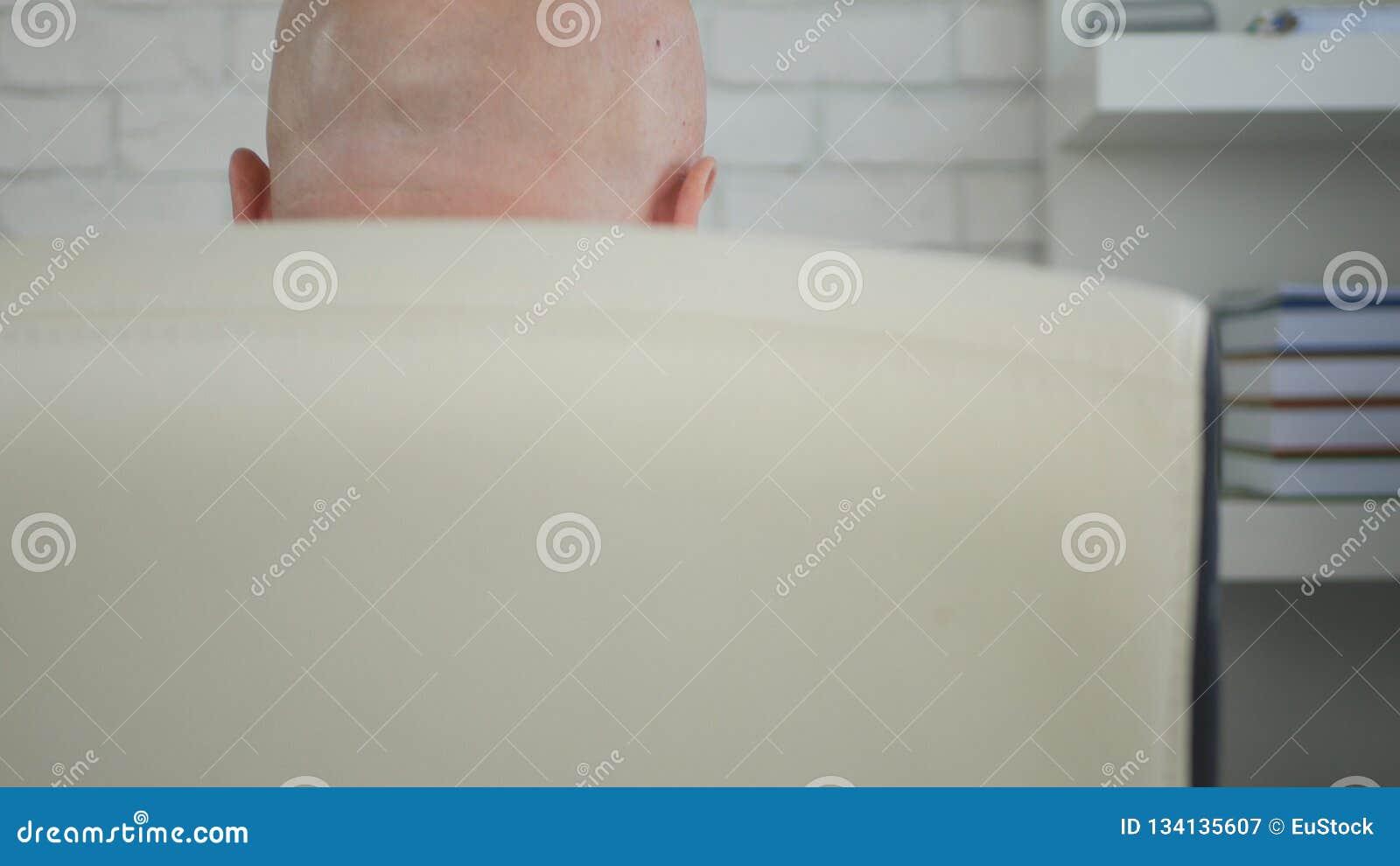Задний взгляд с бизнесменом сидя в стуле менеджера в комнате офиса