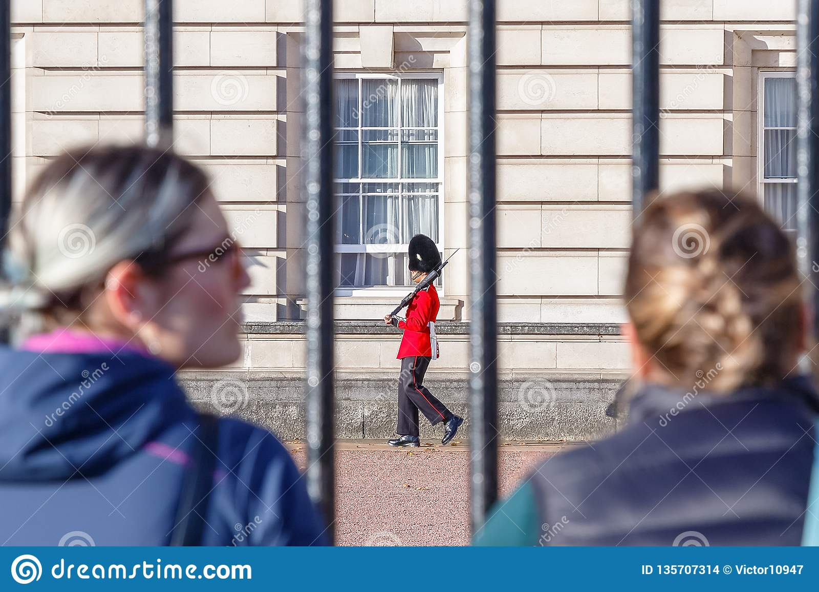 Задний взгляд 2 туристов наблюдая sentry предохранителей Grenadier патрулируя вне Букингемского дворца