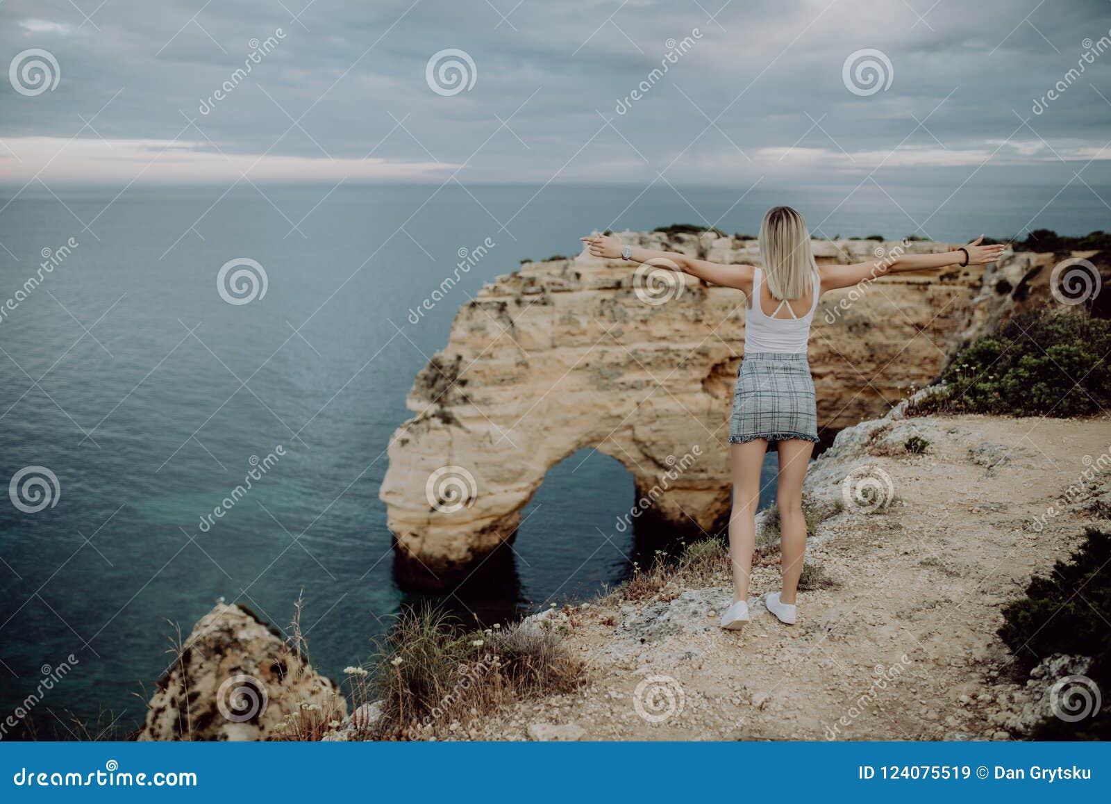 задний взгляд Турист молодой женщины наслаждается красивыми видами Атлантического океана и ландшафтом с побережья в порте