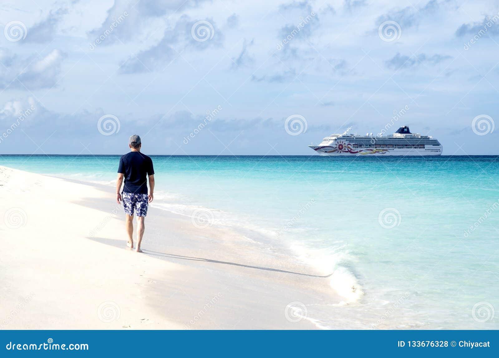 Задний взгляд человека идя на карибский пляж и смотря туристическое судно