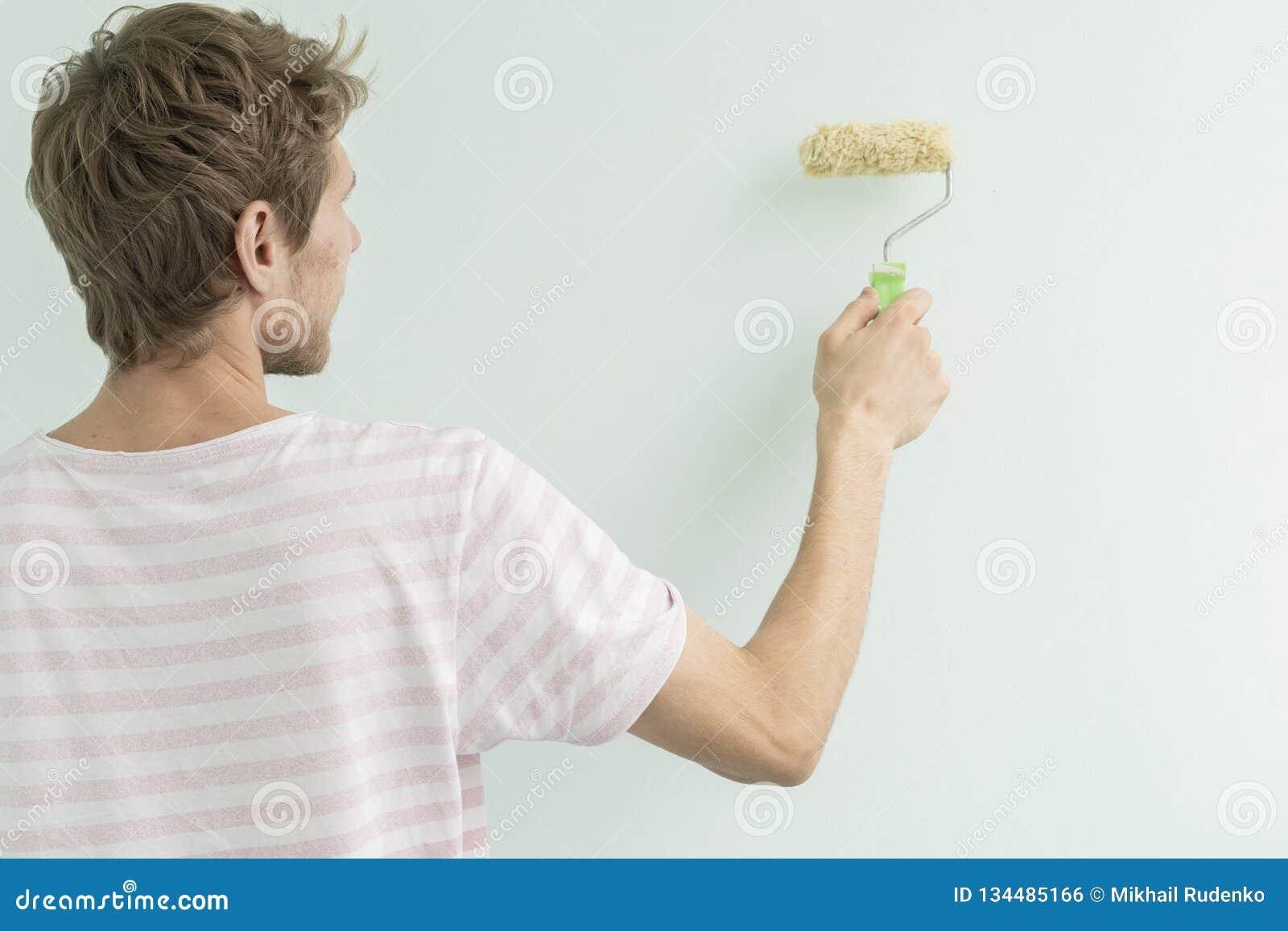 Задний взгляд человека крася стену используя поверхность f пинка ролика