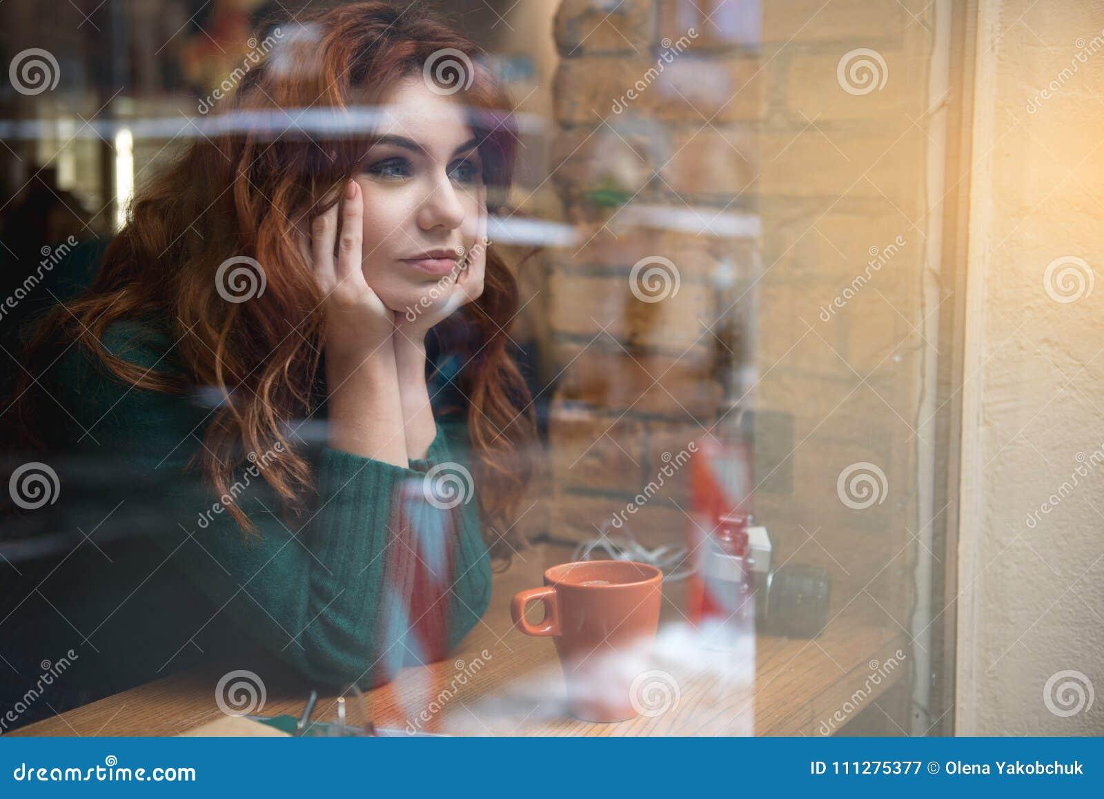 Задумчивая девушка сидя около окна в столовой