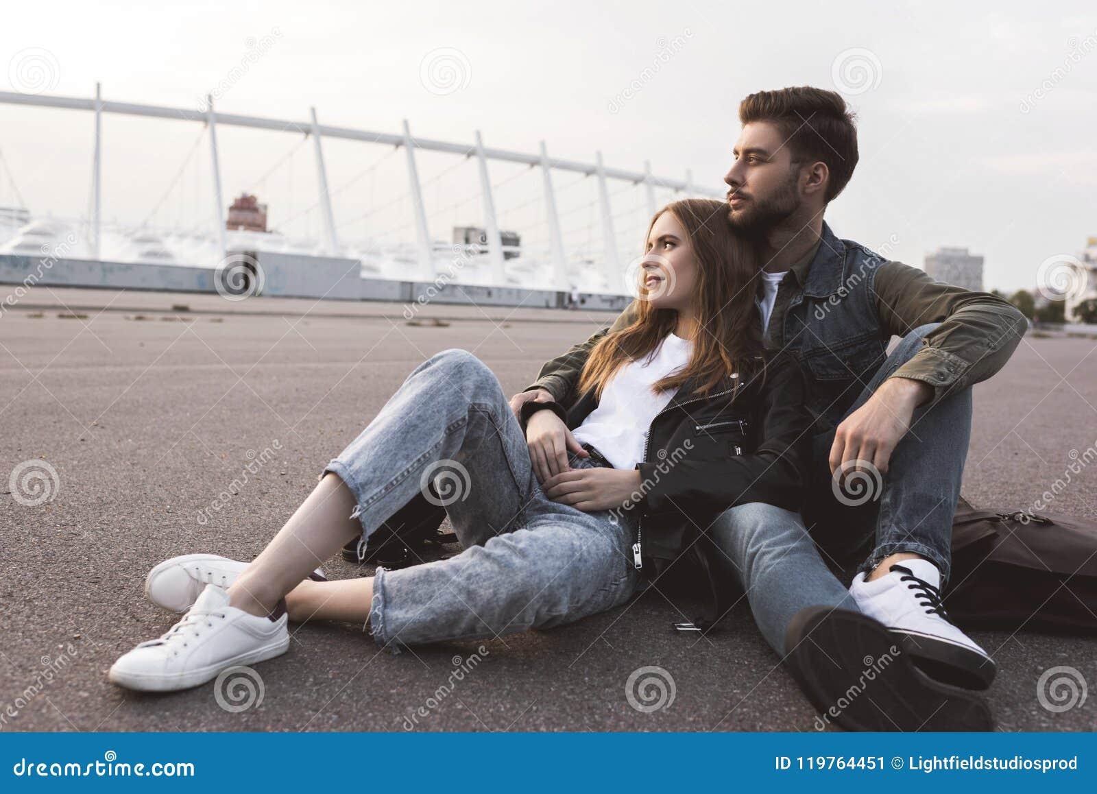 задумчивые пары в вскользь одежде смотря отсутствующий пока отдыхающ