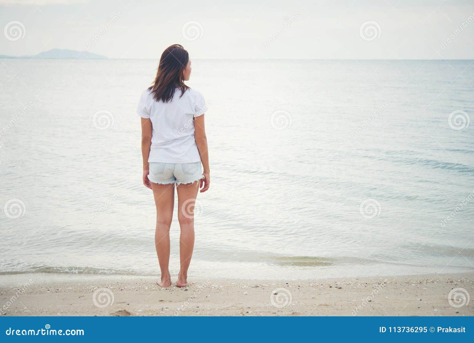 Зад молодой женщины стоя на пляже с barefoot
