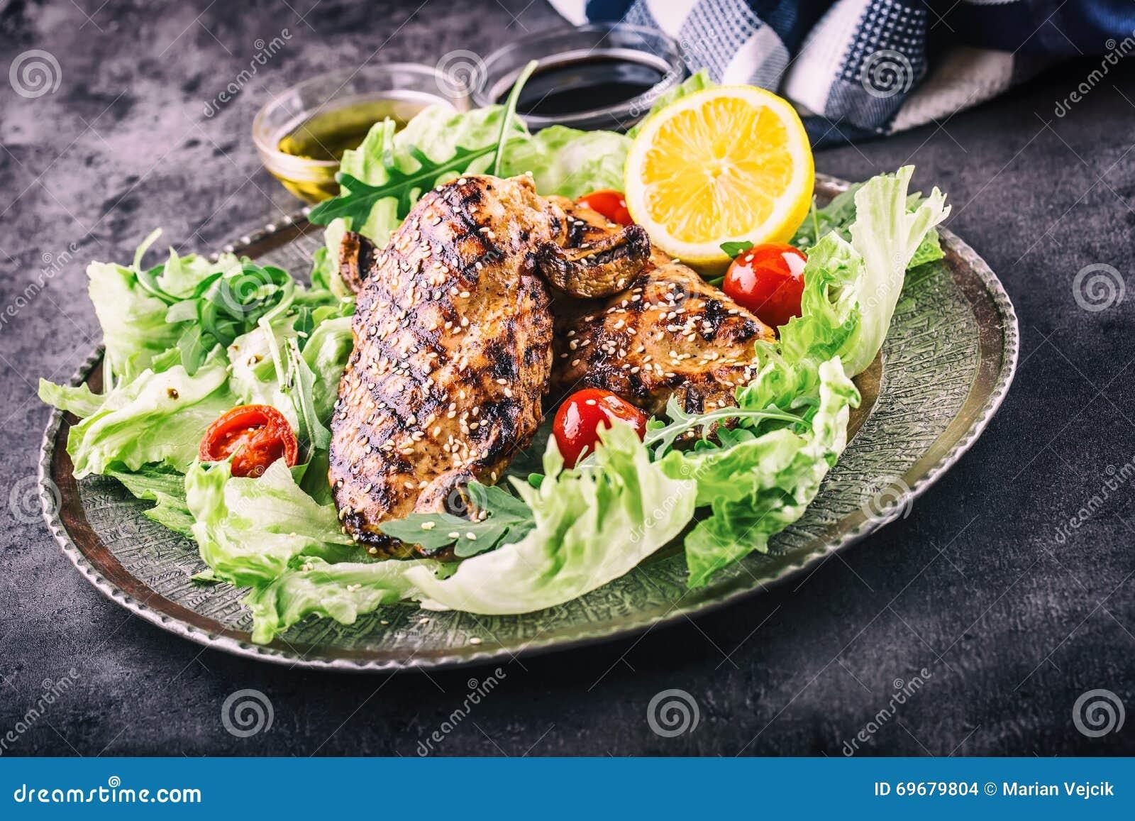 Зажаренная куриная грудка в различных изменениях с травами грибов томатов вишни салата салата отрезала лимон на деревянной доске
