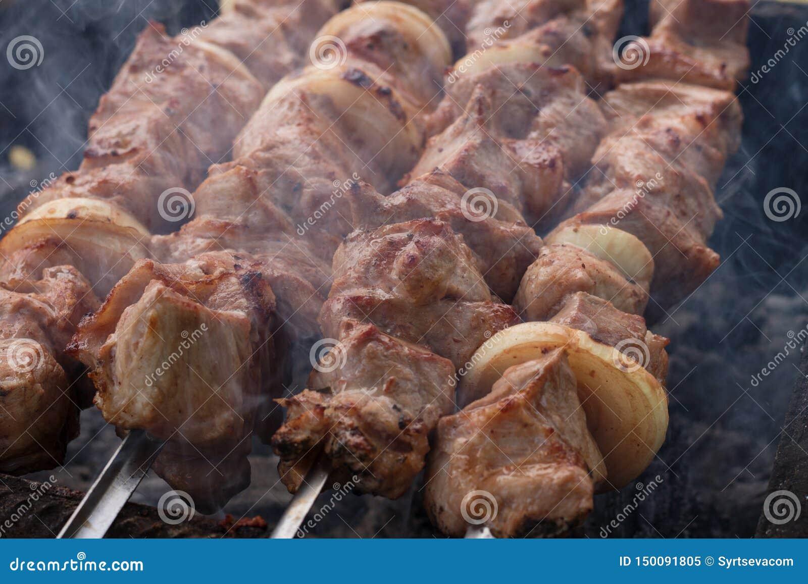 Зажаренное мясо на гриле на природе, на горячих углях, дым