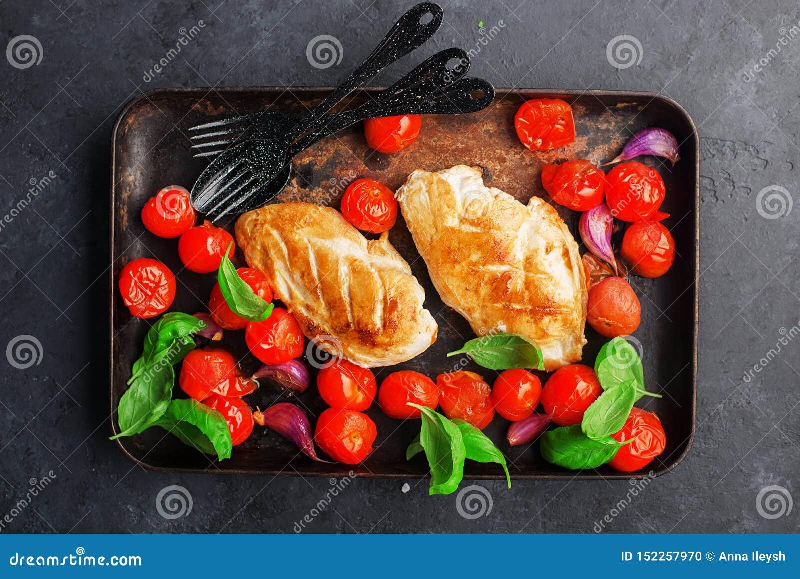 Зажаренное филе куриной грудки с молодым чесноком, томатами вишни на печь листе с листьями базилика Зацепленное блюдо на a