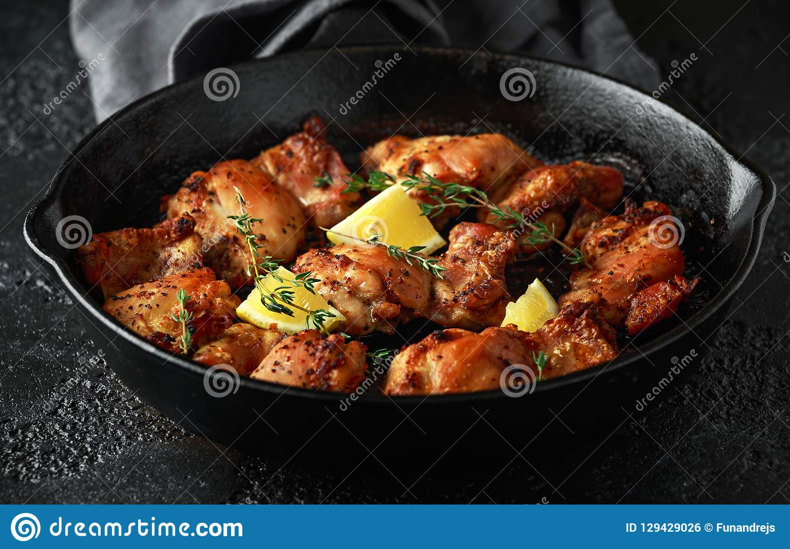 Зажаренные в духовке бескостные skinless бедренные кости цыпленка в шлихте лимона, который и тимиана служат в винтажном skillet л