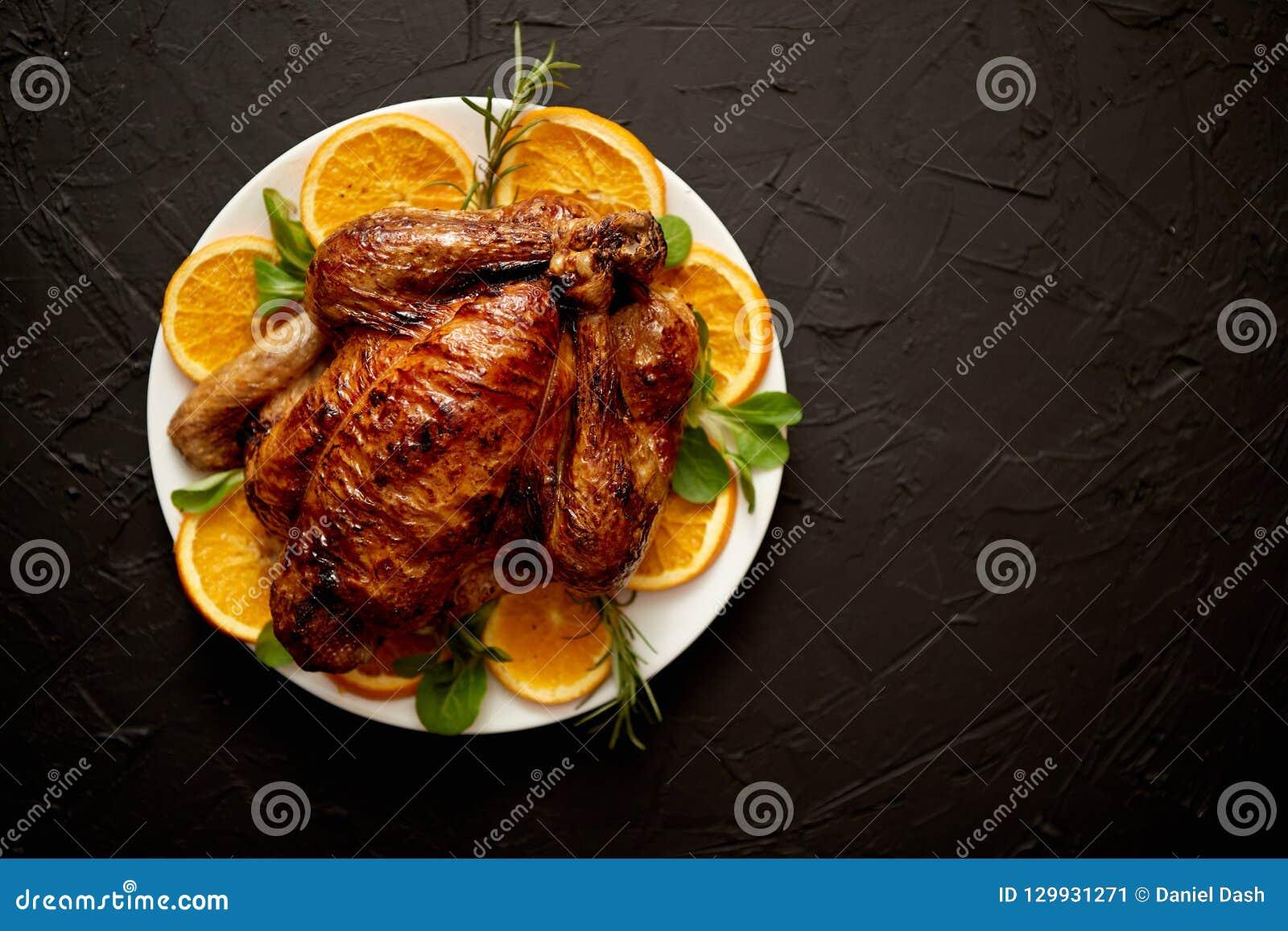 Зажаренные в духовке весь цыпленок или индюк служили в белой керамической плите с апельсинами