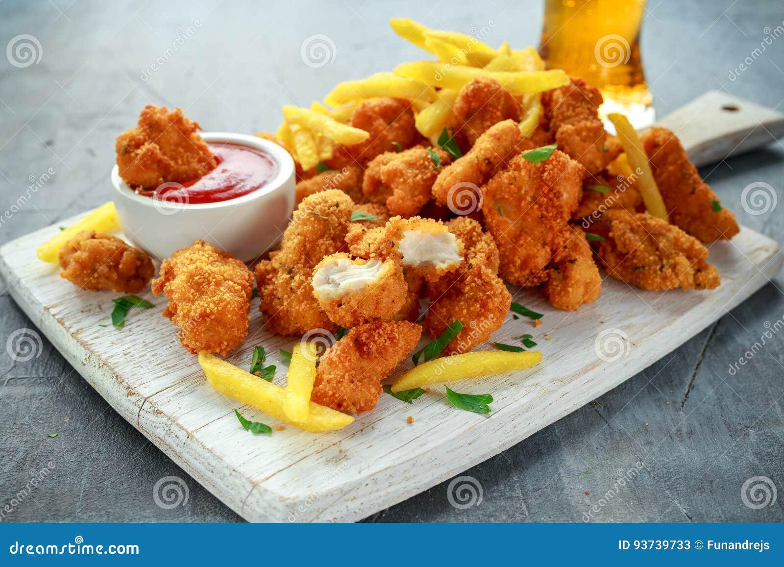 Зажаренные кудрявые наггеты цыпленка с французскими фраями, кетчуп и пивом на белой доске