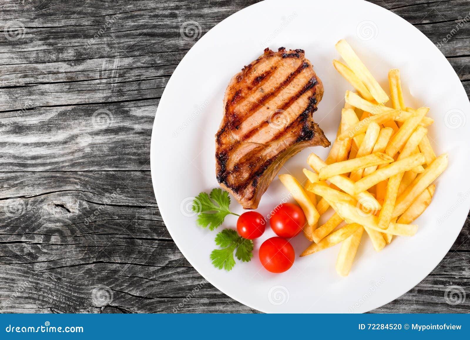 Download Зажаренные свиные отбивние на белом блюде с французскими фраями Стоковое Фото - изображение насчитывающей brougham, гарнируйте: 72284520