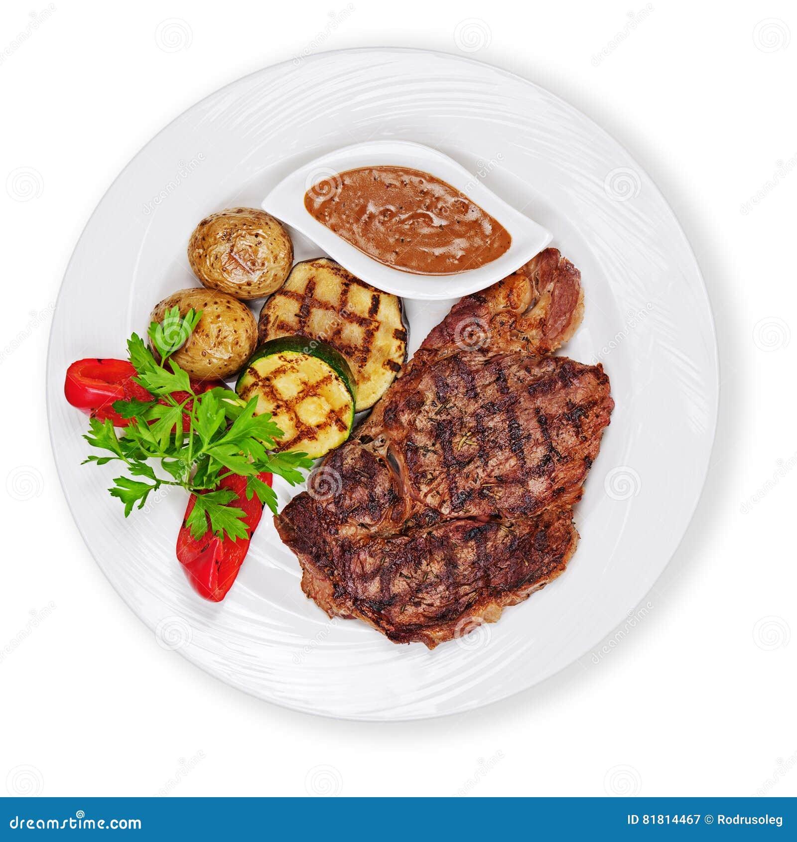 Зажаренные стейк, картошки и овощи изолированный на белой предпосылке