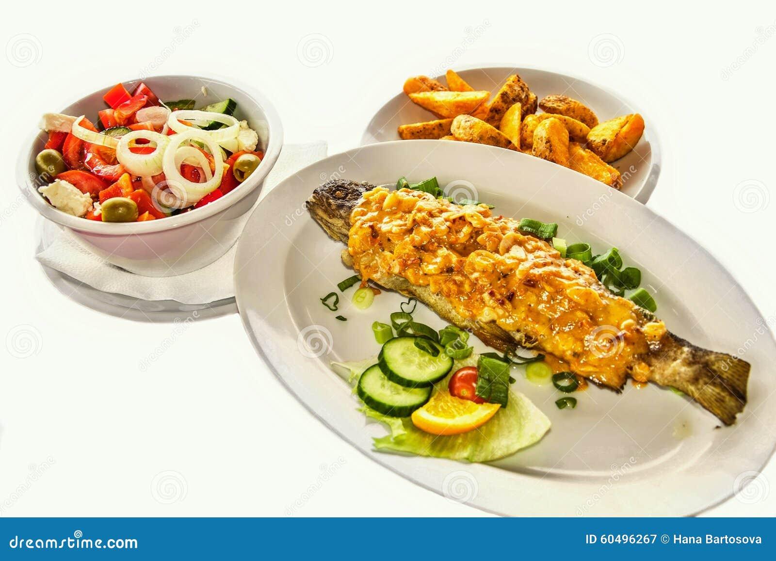 Зажаренные форель, салат и картошки