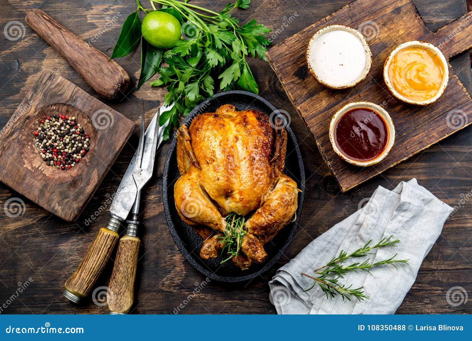 Зажаренный в духовке цыпленк цыпленок с розмариновым маслом служил на черной плите с соусами на деревянном столе, взгляд сверху