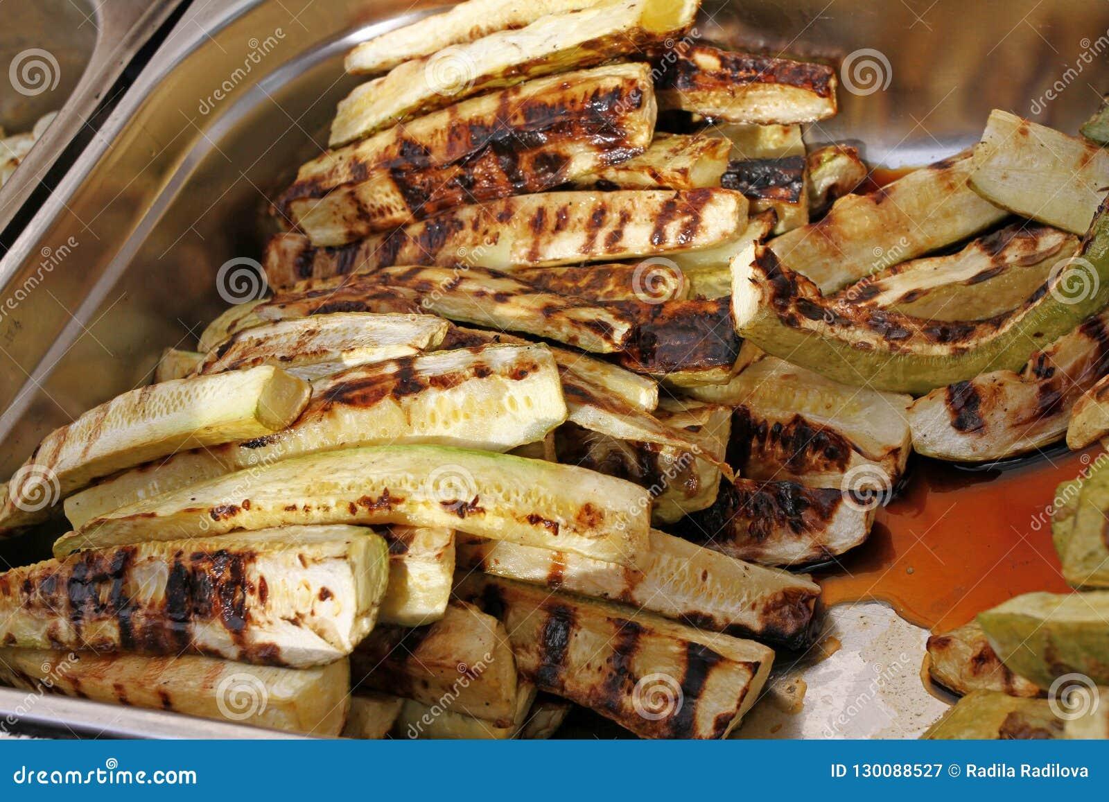 Зажаренный органический цукини на bbq Овощи на обоях барбекю Vegetable текстура предпосылки Зажаренный зеленый цукини зажжено
