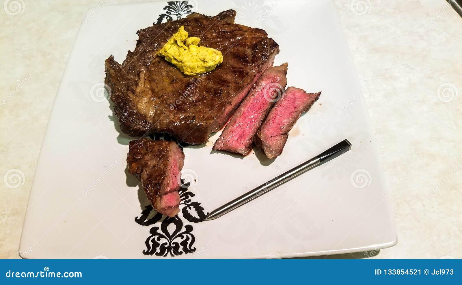Зажаренный стейк, сваренное средство, с кафем de Парижем beurre и термометром bluetooth, поверх плиты