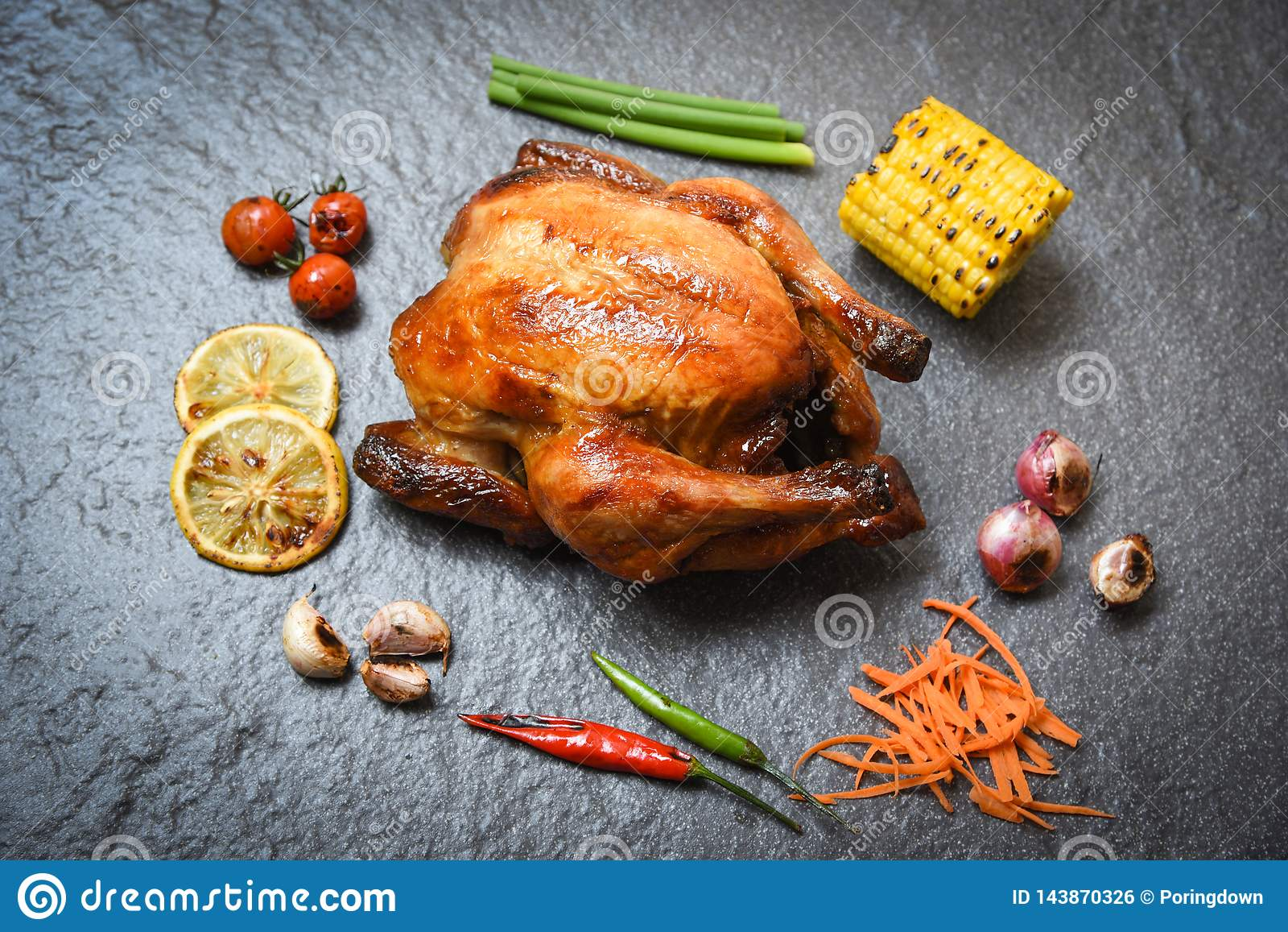 Зажаренный цыпленок на предпосылке плиты темной с зажаренными чилями лимона томатов пряными