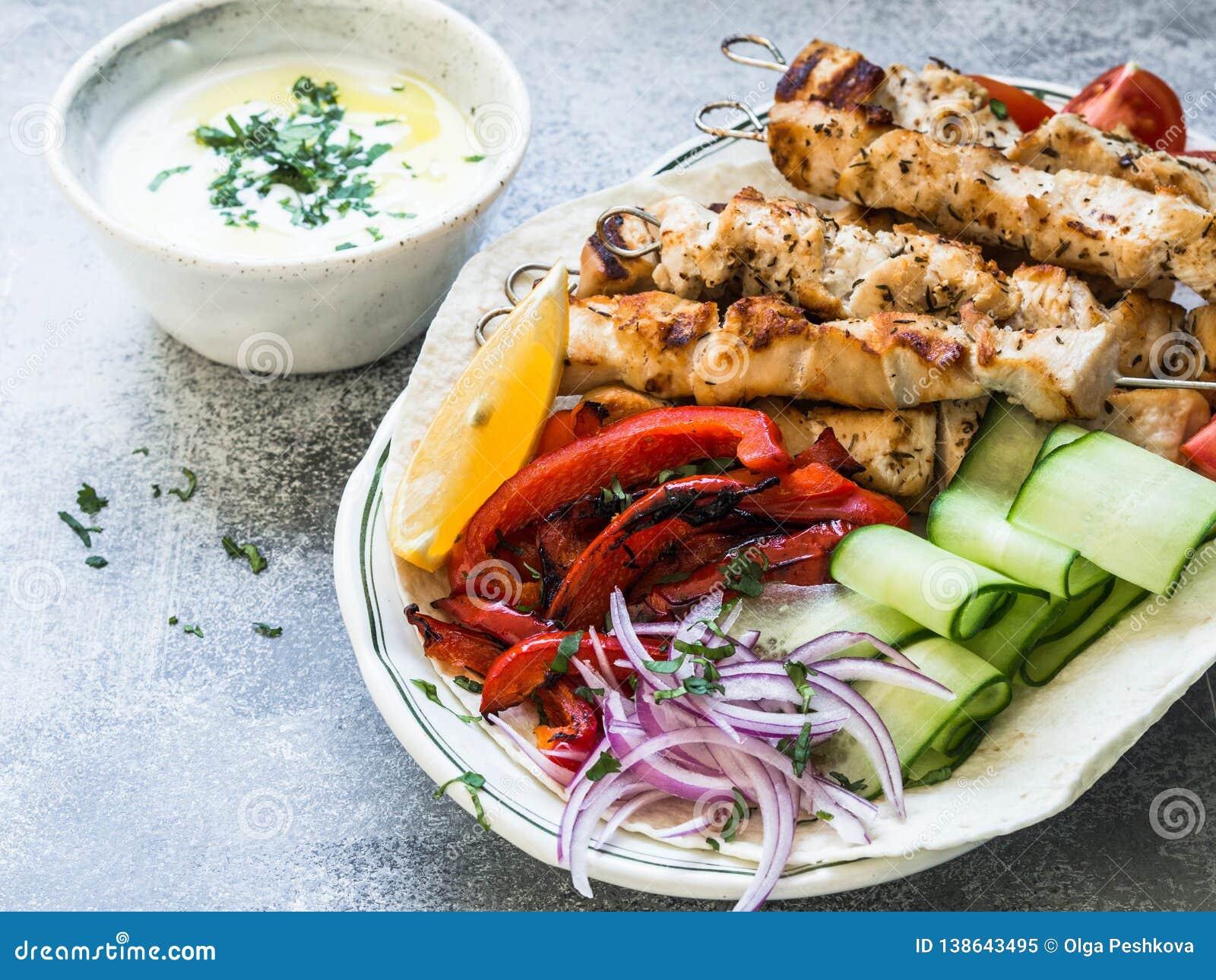 Зажаренный цыпленок на протыкальниках металла со свежими овощами на пите и греческом соусе в шаре на серой предпосылке греческо