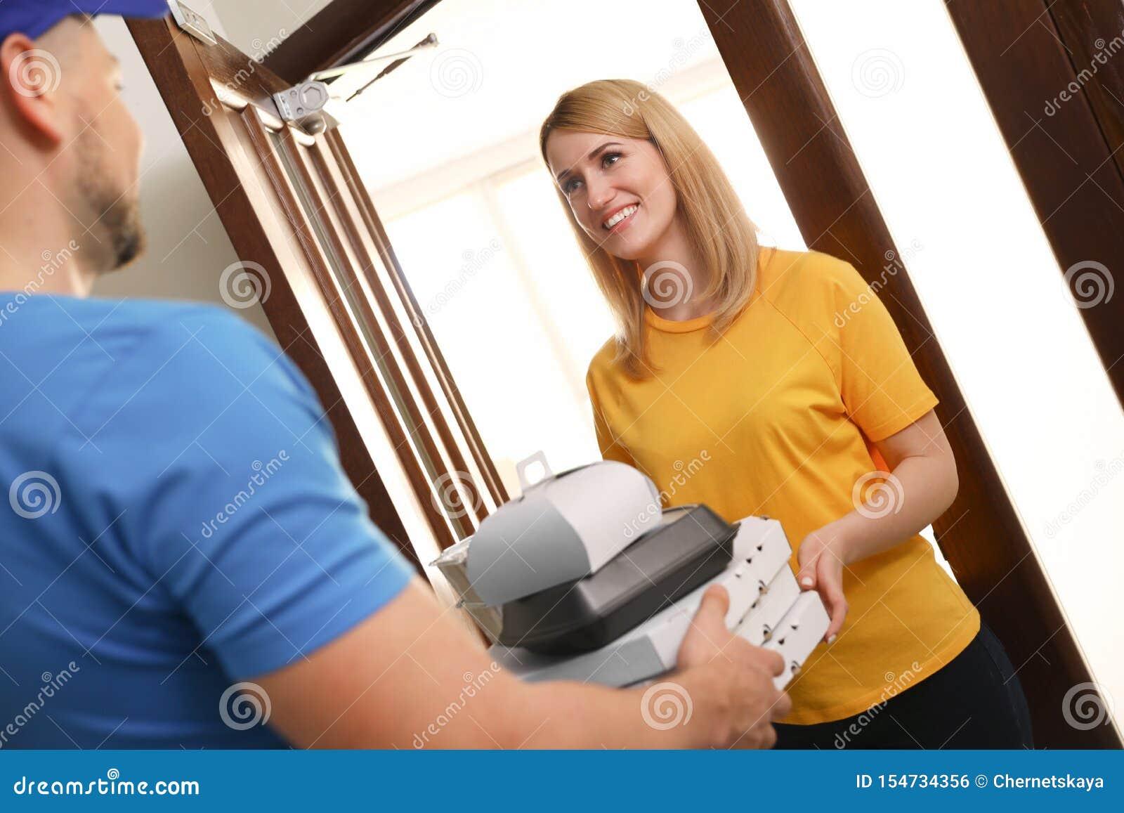 Заказ женщины получая от курьера на двери Доставка еды