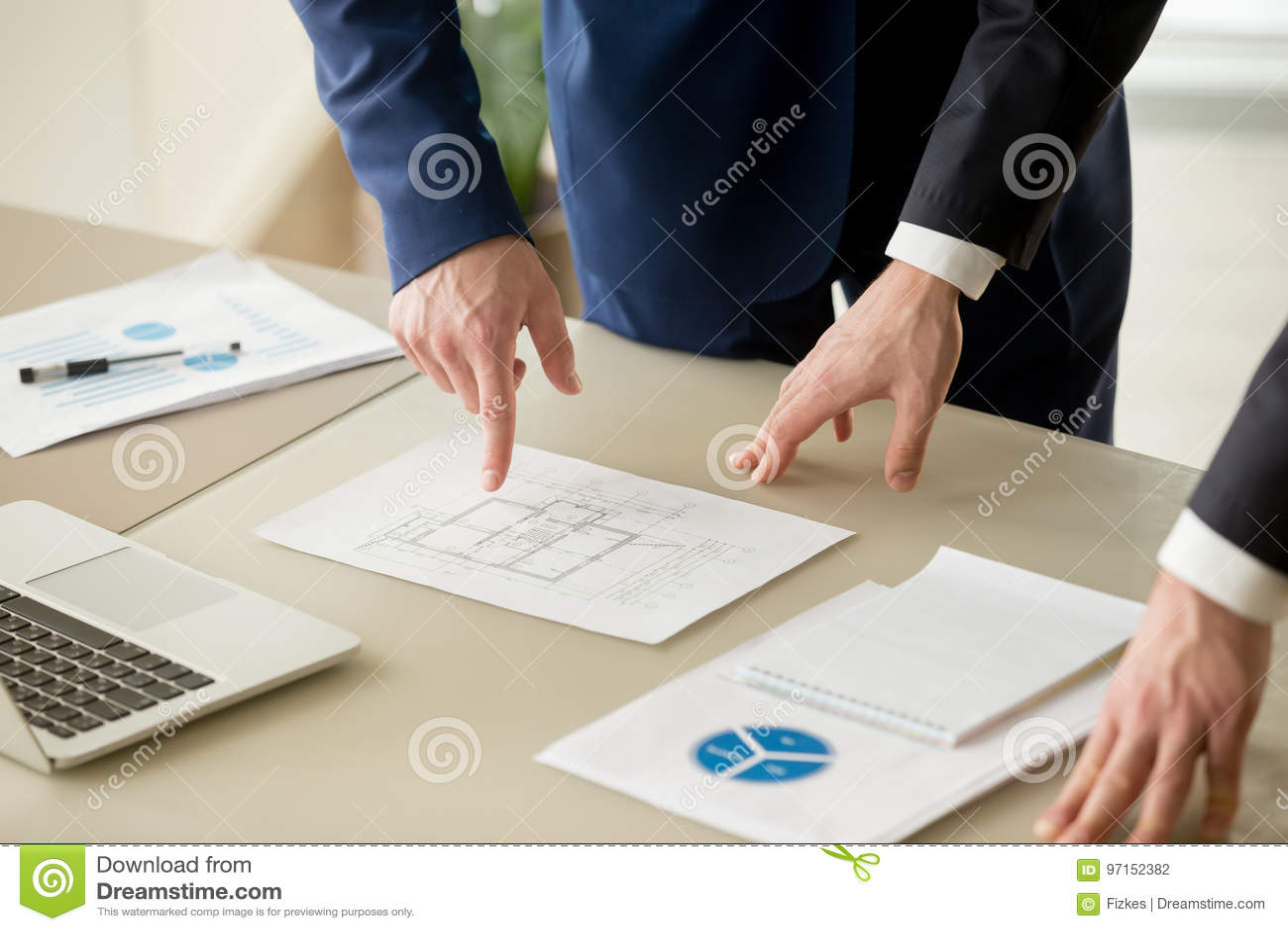 Закройте вверх бизнесменов обсуждая строящ план, стоимость имущества