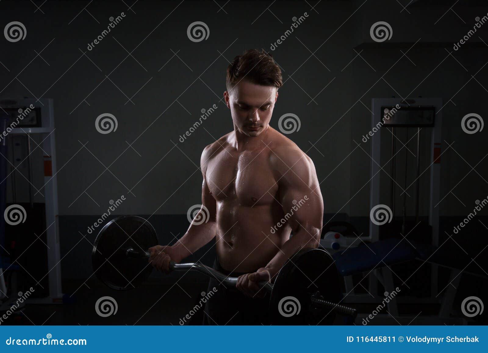 Закройте вверх весов молодого мышечного человека поднимаясь над темной предпосылкой