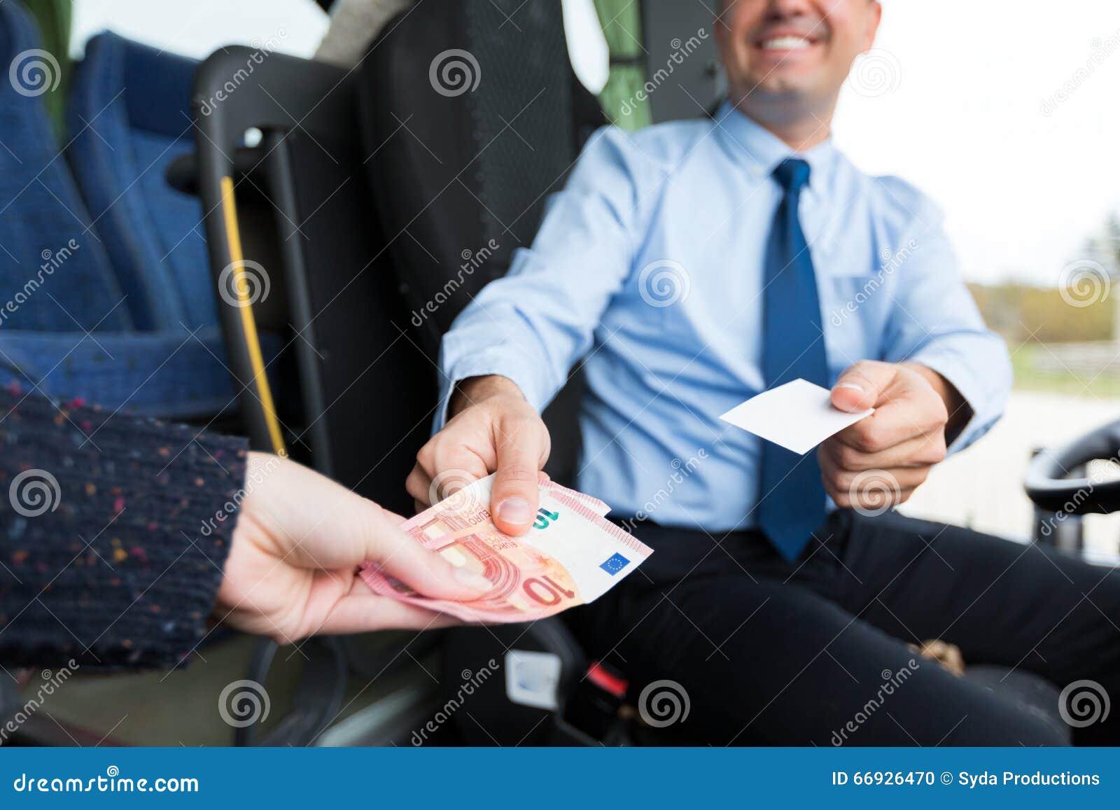 Закройте вверх водителя автобуса продавая билет к пассажиру