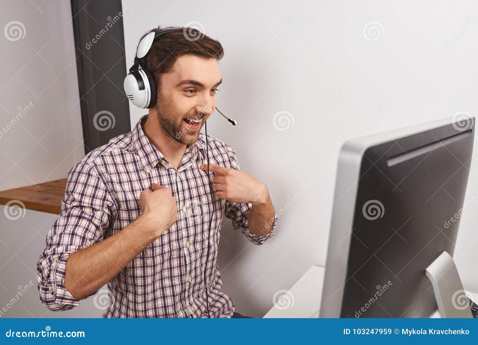 Закройте вверх жизнерадостного молодого смешного симпатичного мужского gamer играя Онлайн-игры на персональном компьютере в наушн