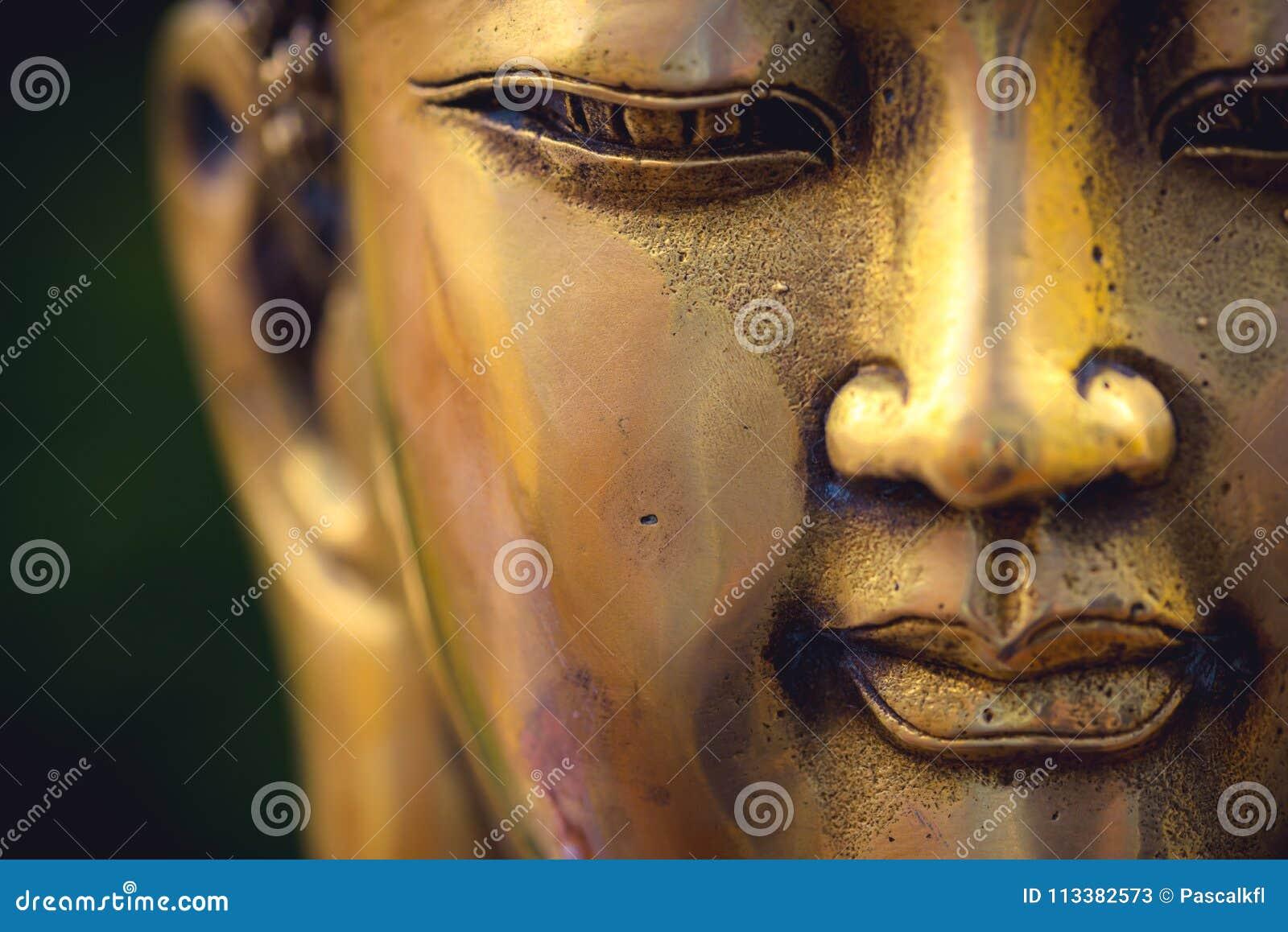 Закройте вверх золотой покрашенной головы Будды на черной предпосылке