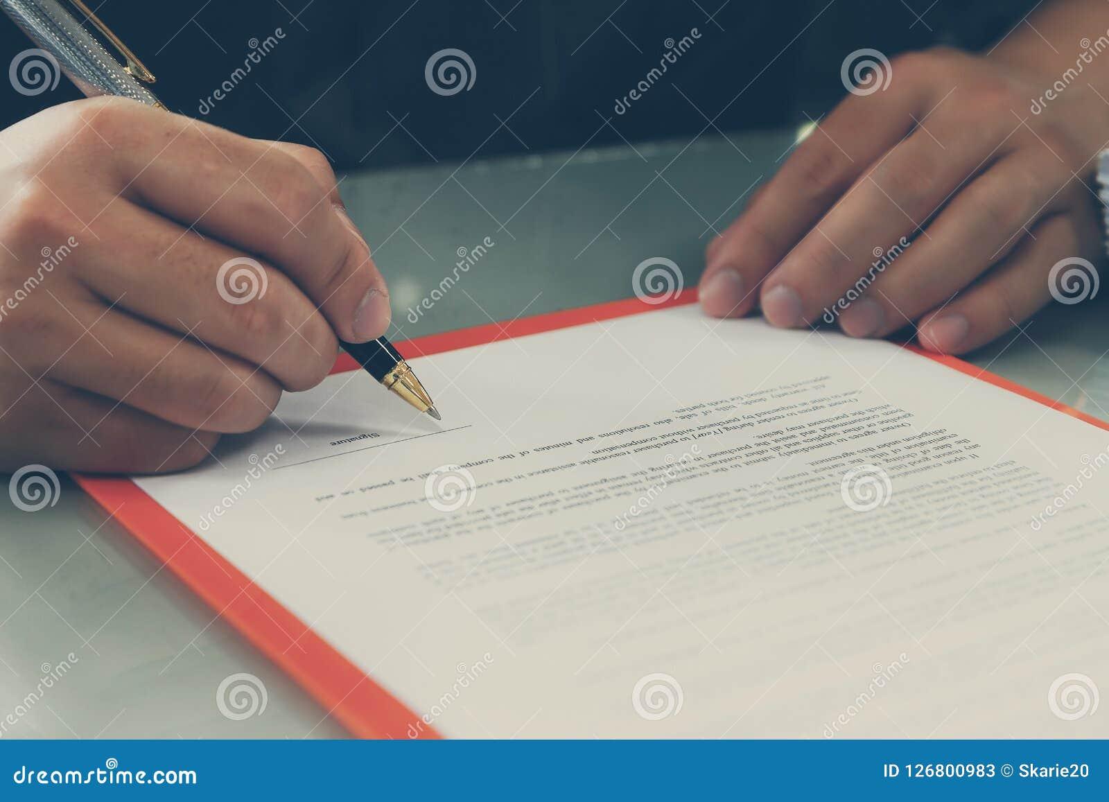 Закройте вверх контракта бизнесмена подписывая делая дело