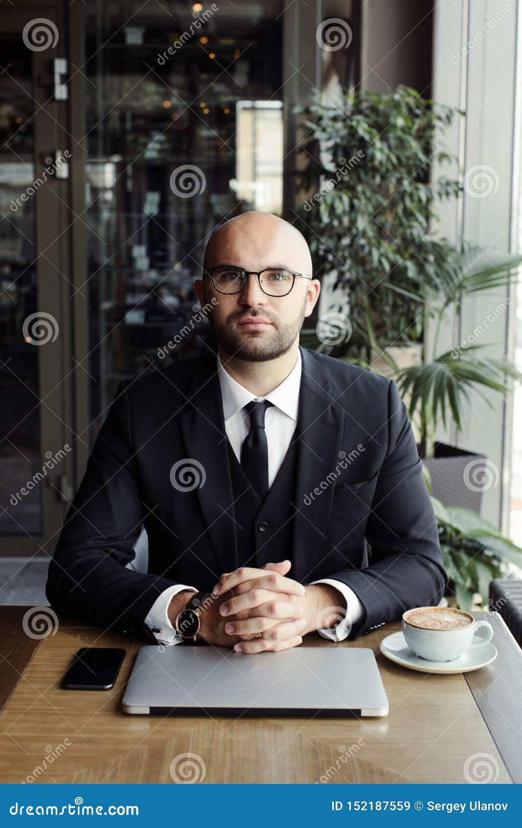 Закройте вверх красивого бизнесмена, работающ на ноутбуке в ресторане
